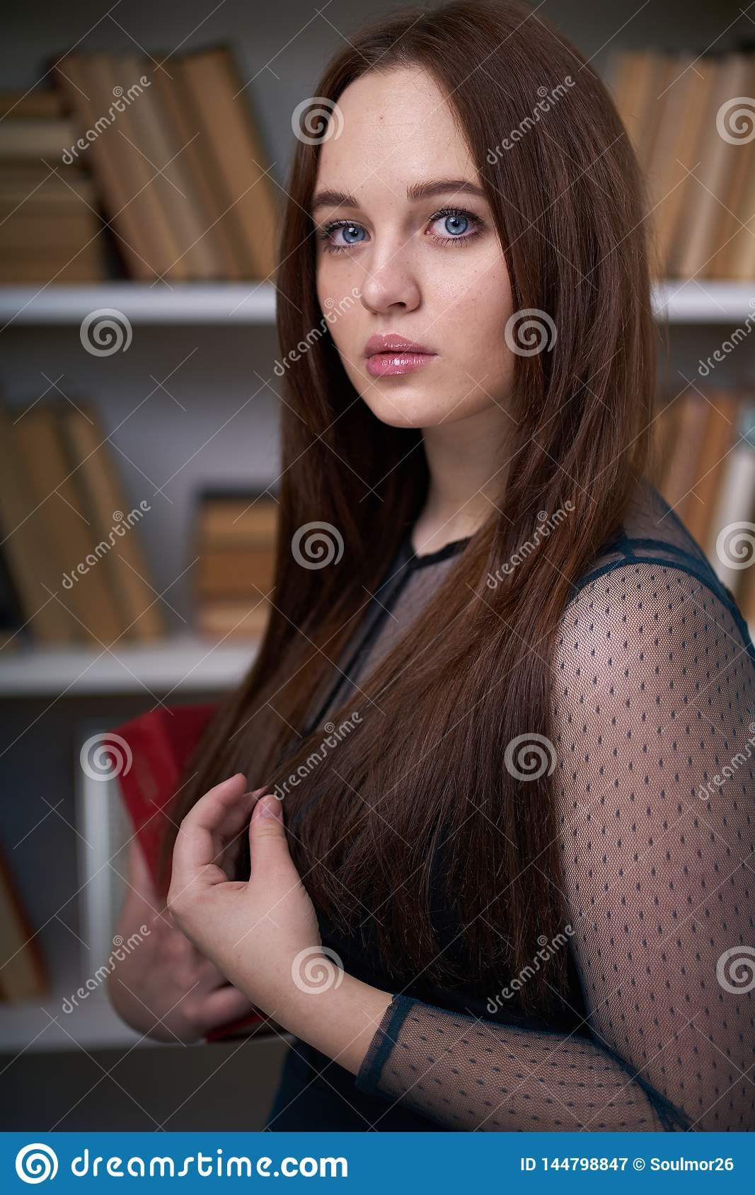 Pretty Female Student Surrounded by Library Books