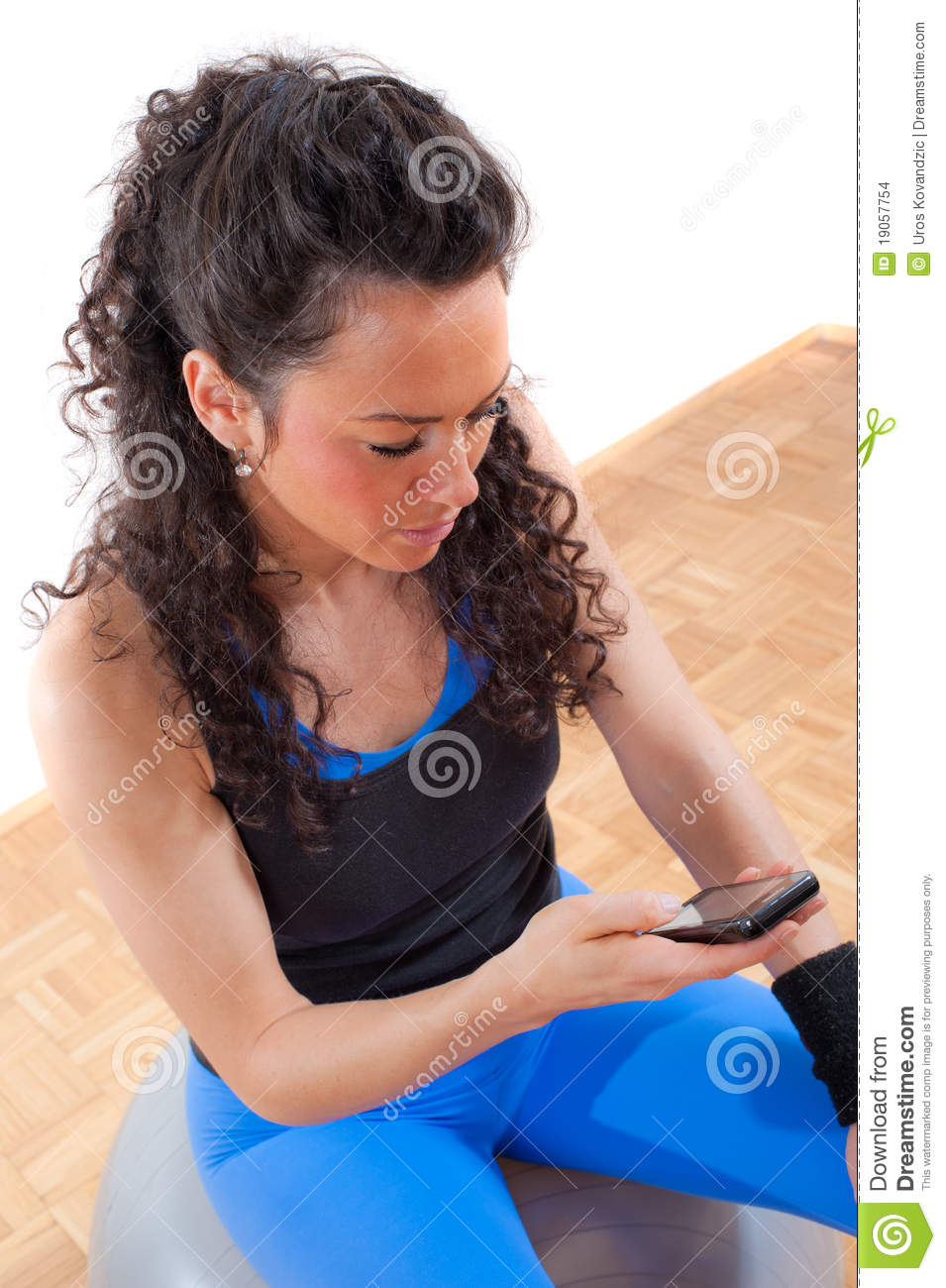 Pretty fitness girl taking a break with cellphone