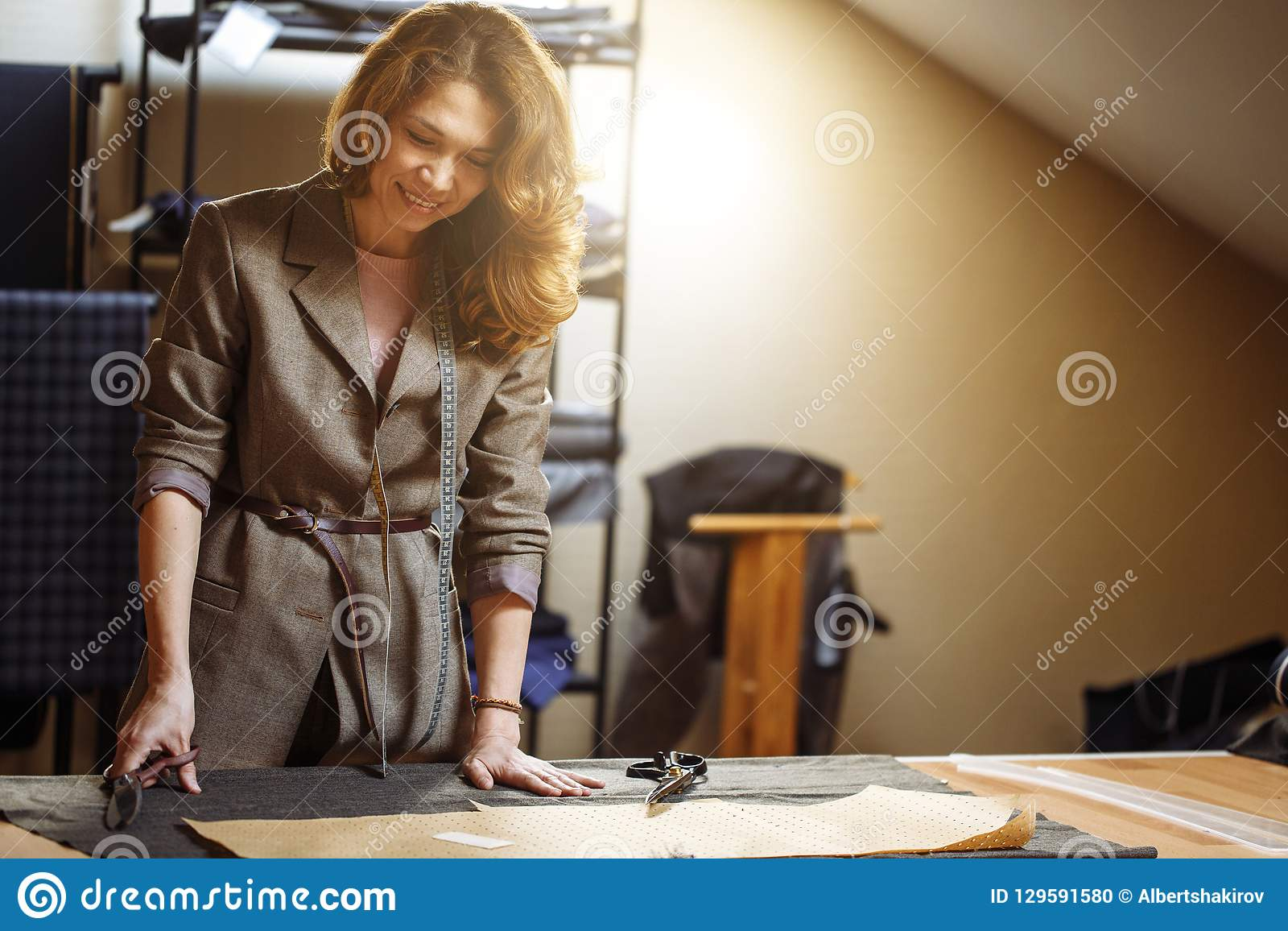 Pretty focused young woman fashion designer cutting grey fabric in studio