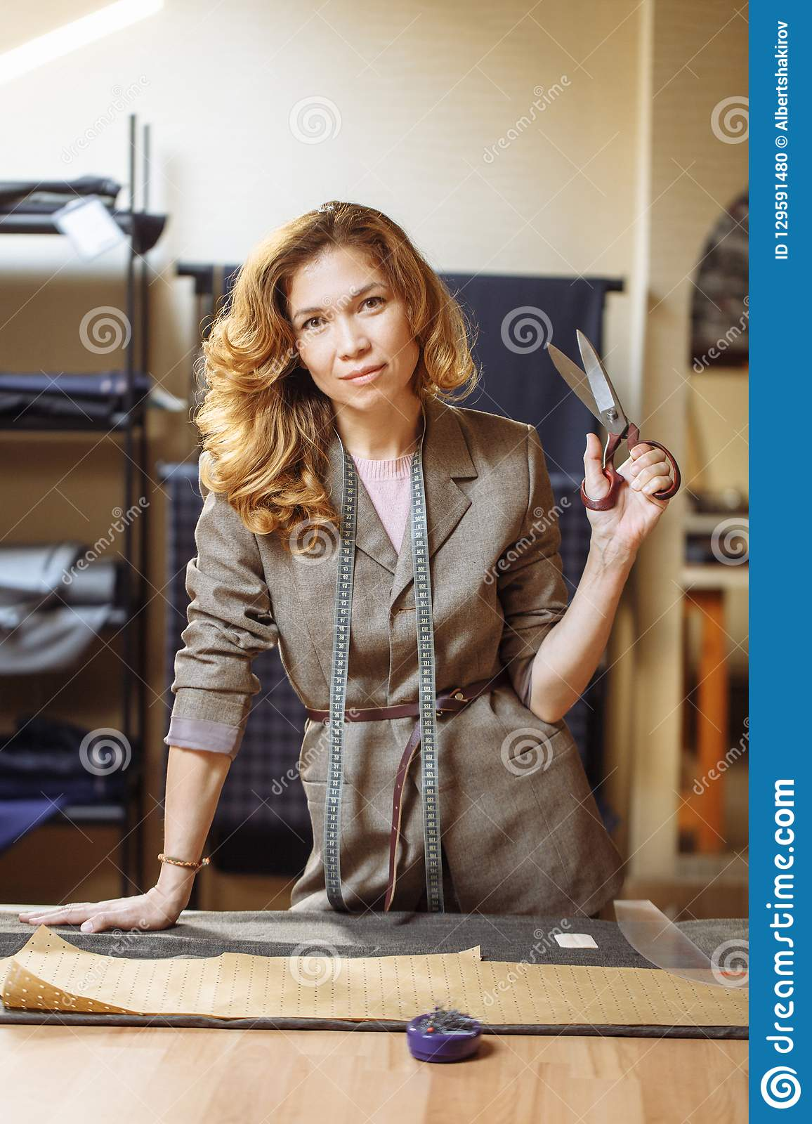 Pretty focused young woman fashion designer cutting grey fabric in studio