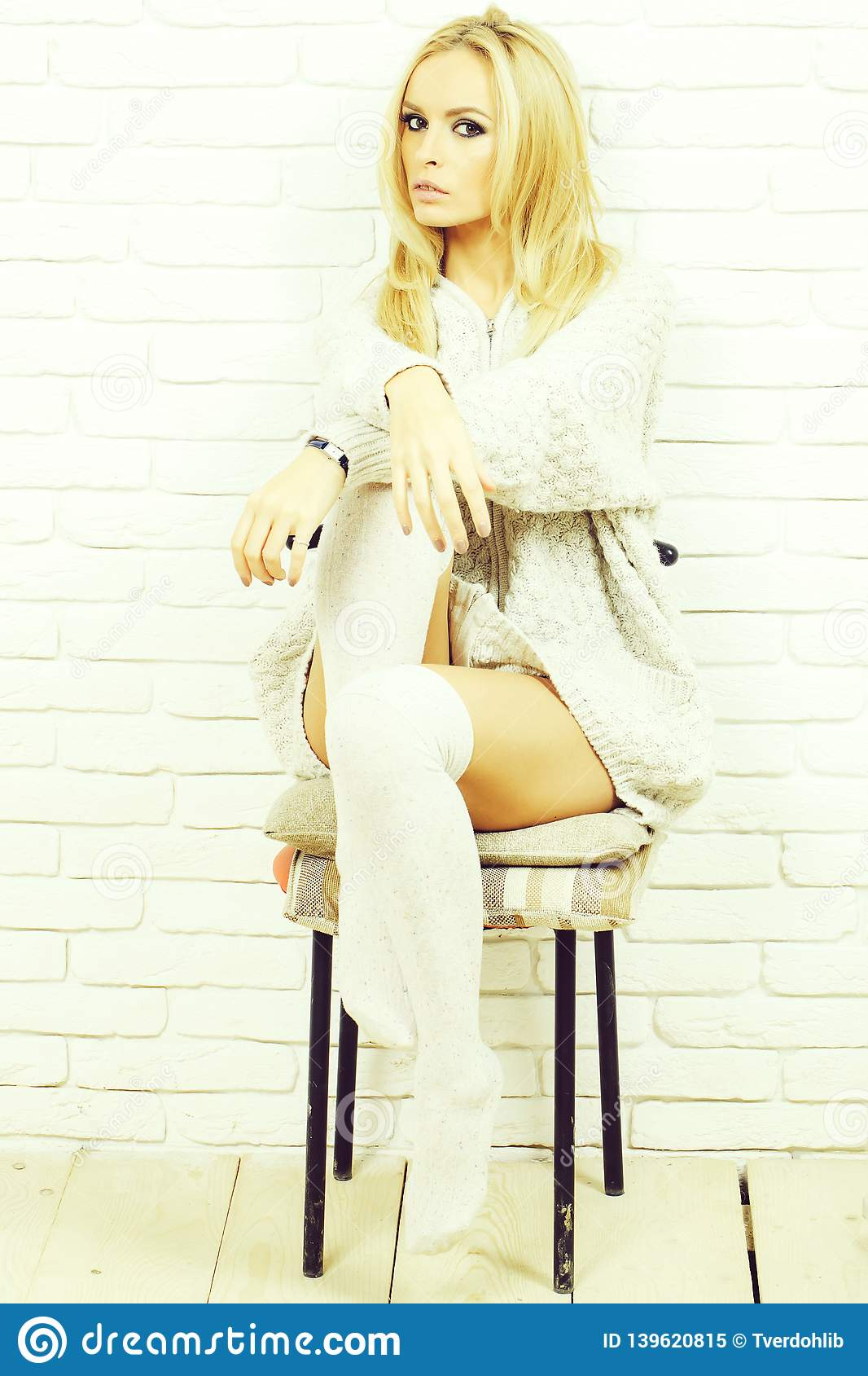 b8f82f54685f Pretty girl or beautiful cute woman fashion model with blond hair in  knitted sweater sits on chair on white brick wall