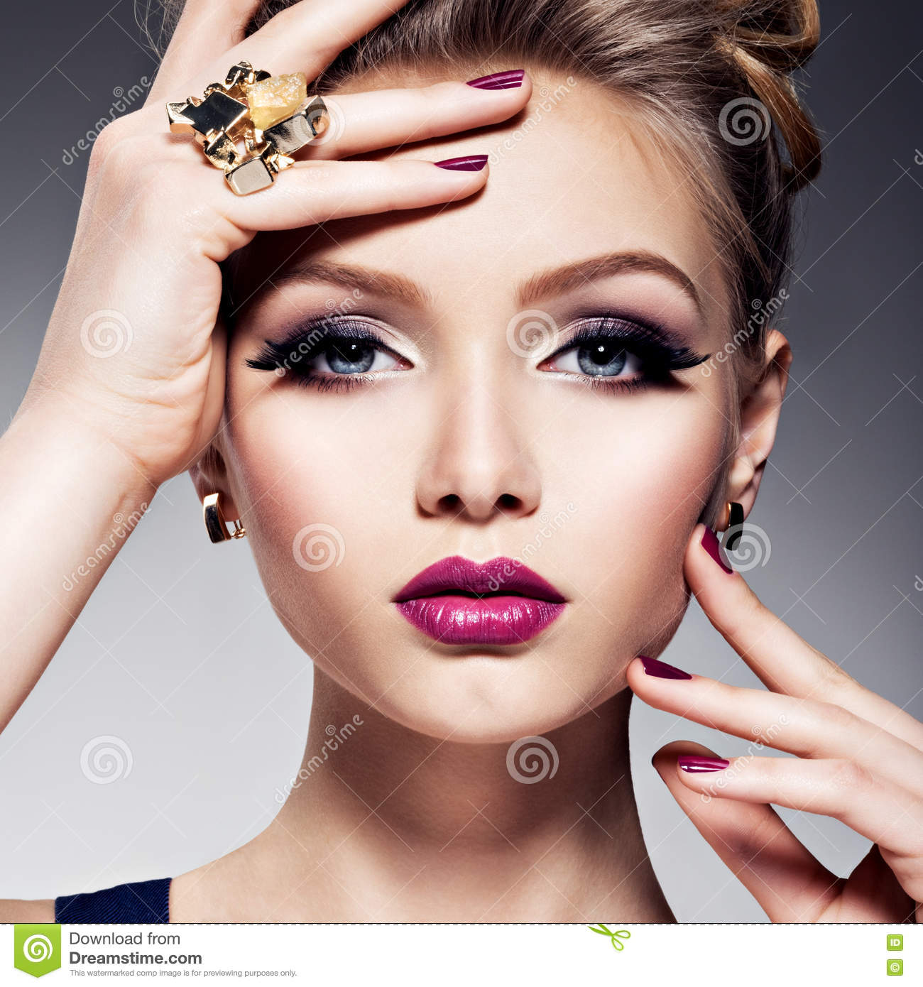 Pretty girl with beautiful face bright make-up and gold jewelry