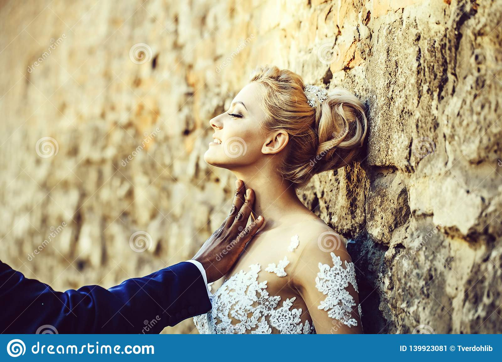 Pretty girl or cute bride with beautiful makeup and blond hair, hairstyle, in white wedding dress with hand of african American male on neck on sunny day ...