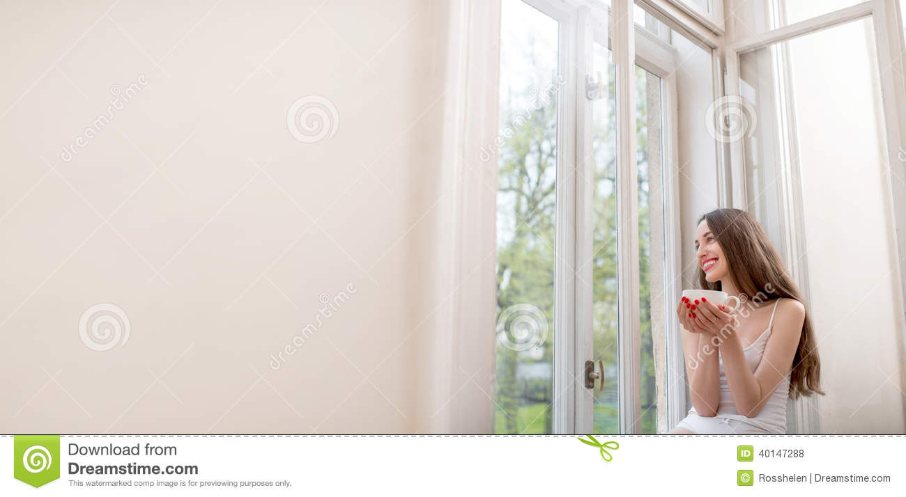 Pretty Girl Sitting Near The Window And Looking Out The