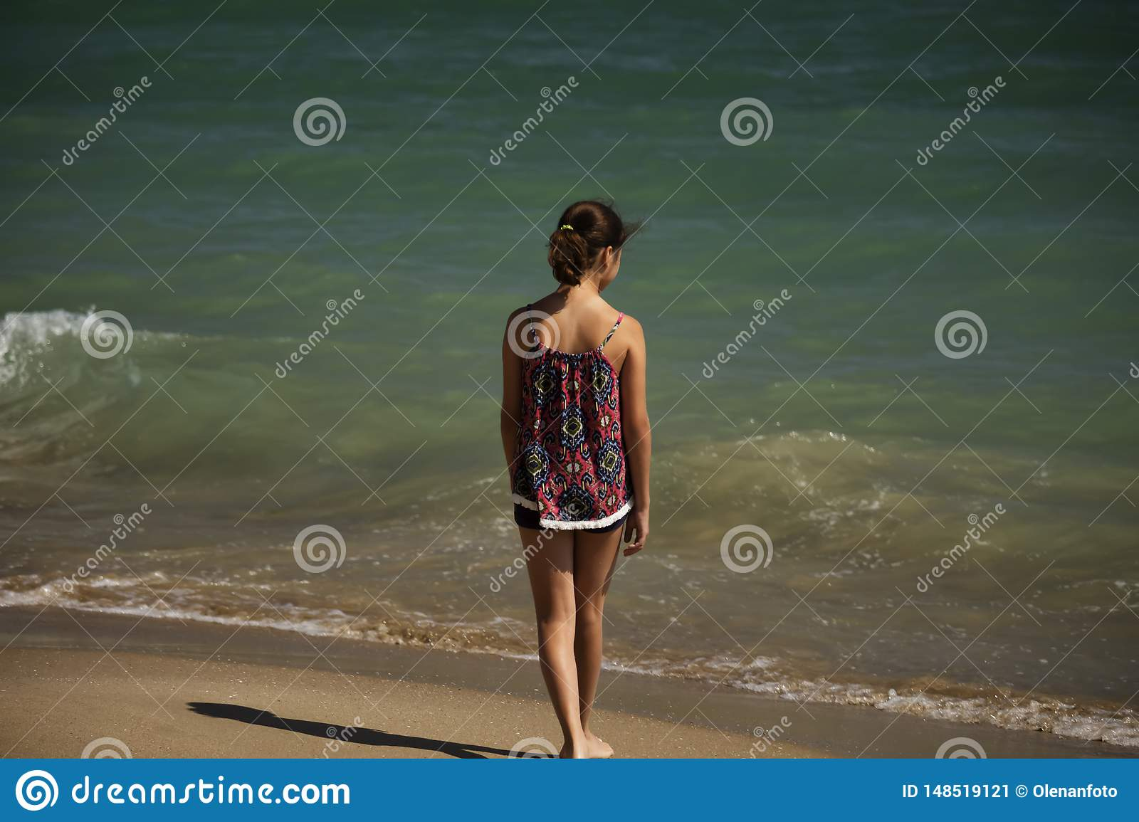 A pretty girl standing  on the beach and looking far into the sea, soft fockus