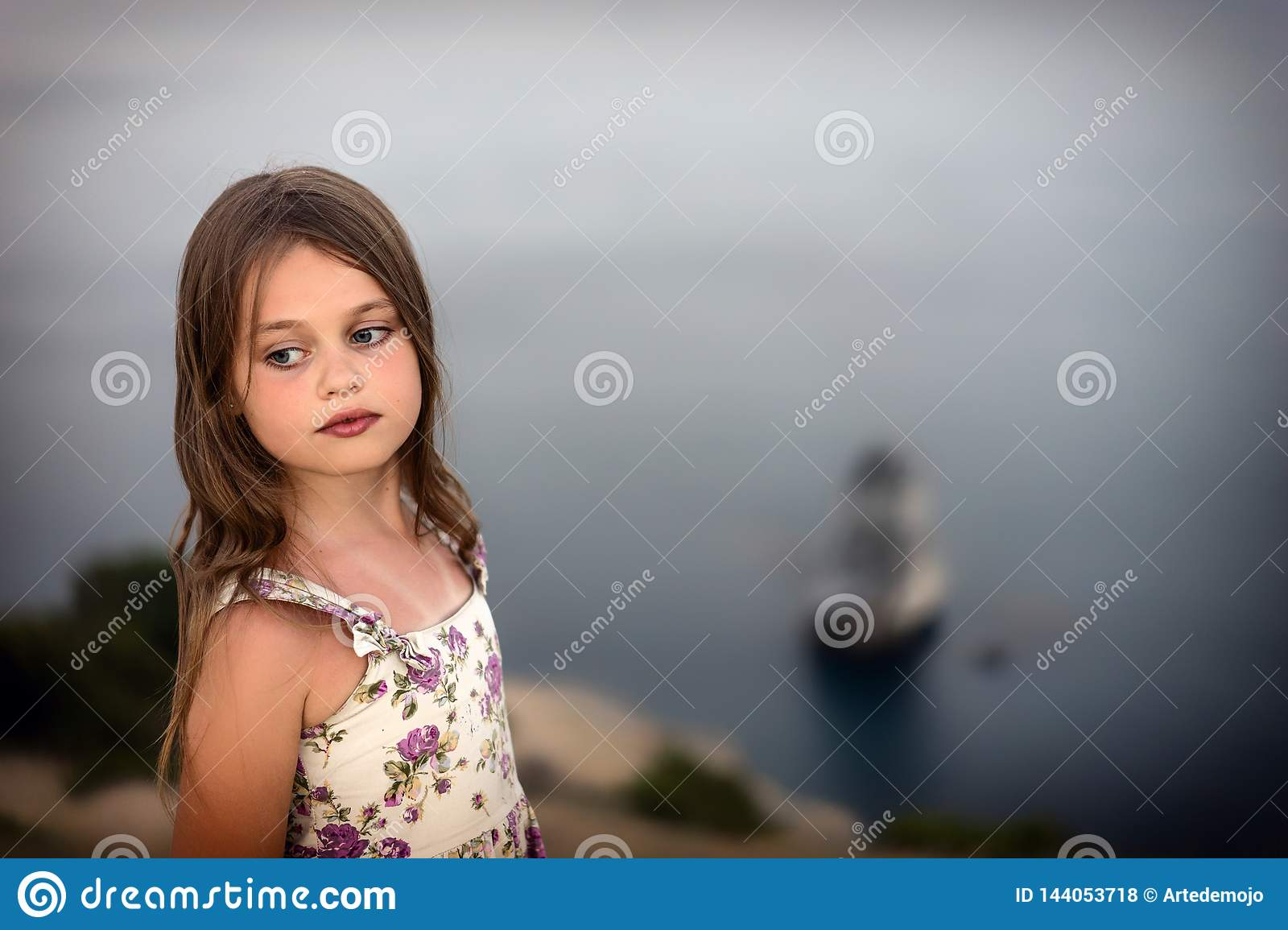 Pretty girl in summer dress with wet hair stands thoughtfully by the sea.