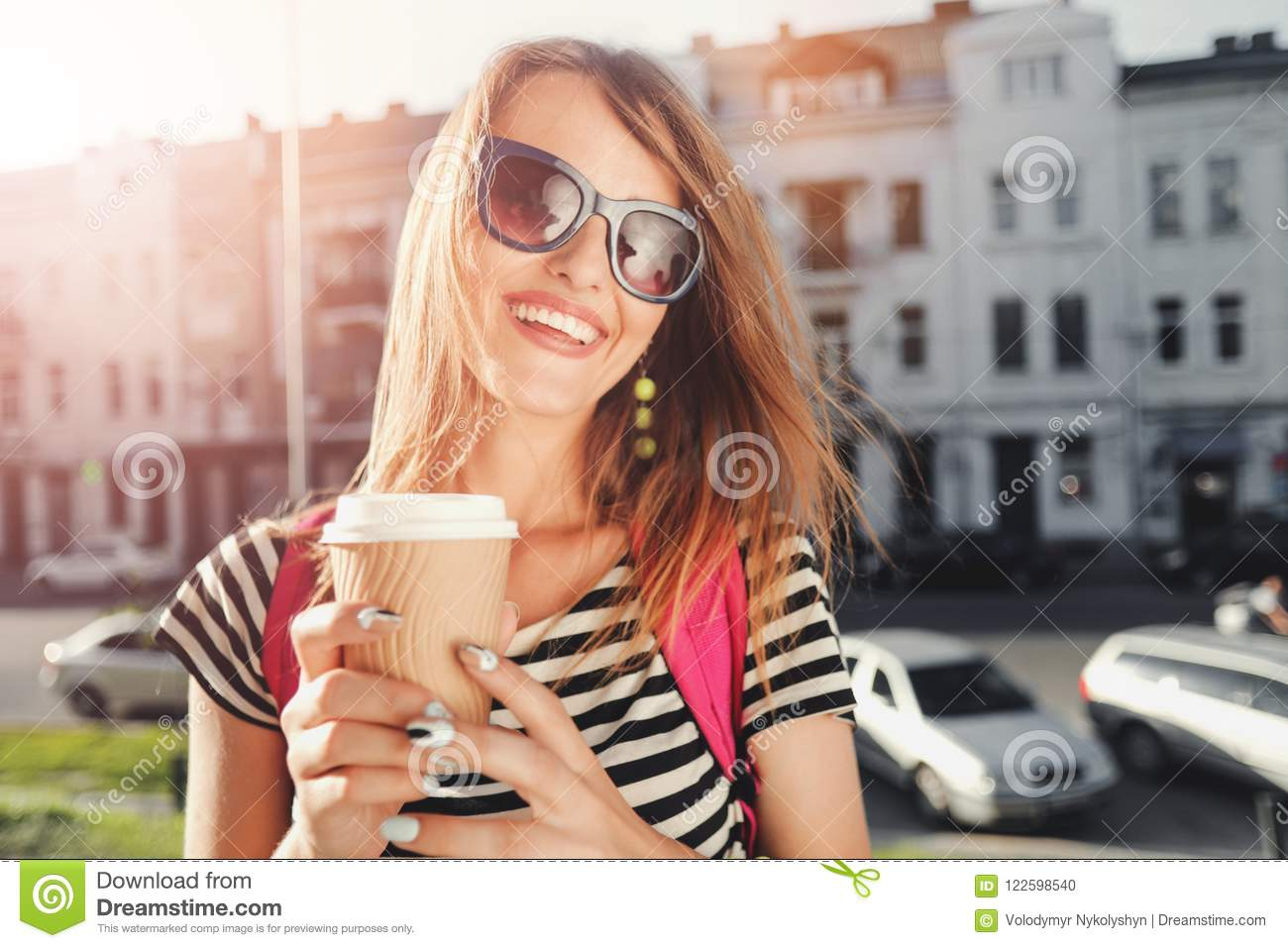 63ffd5017f8c Portrait of closeup teenager long-hair girl in sunglasses drinking coffee  and walking on the street with pink backpack. More similar stock images