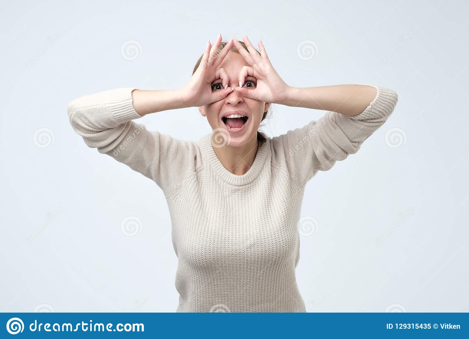 Pretty girl with surprised face holding fingers near eyes like glasses. Mask  like super hero