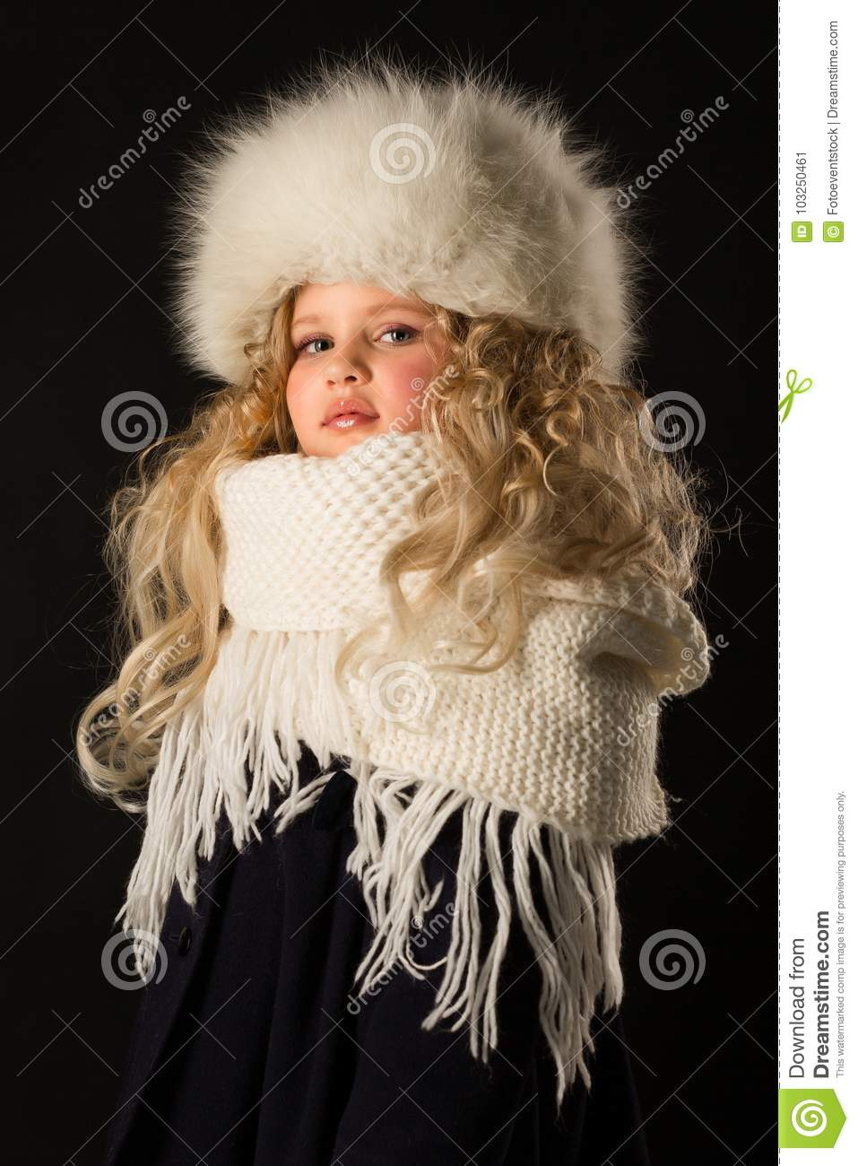 09deda88971303 Vertical picture, isolated on black, beautiful caucasian blonde little girl  in dark blue coat, white scarf and white fur hat, serious look