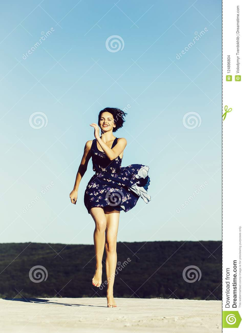 47a827142a9b6 Pretty girl young beautiful woman brunette slim model with bare feet in  blue dress jumps on sky background