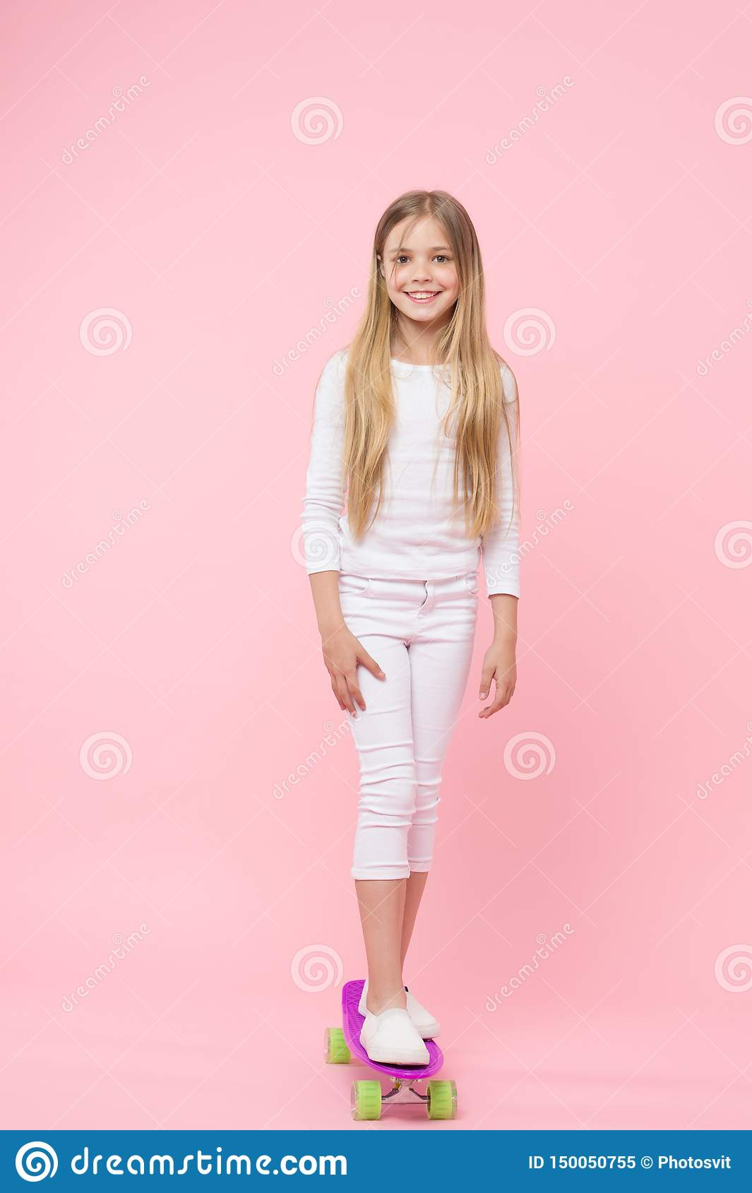 A pretty good skater girl. Cute small girl standing on skateboard on pink background. Little girl child on violet penny