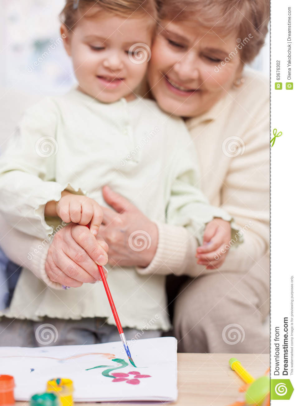 Pretty grandparent is teaching child to paint stock photo for Teaching kids to paint on canvas
