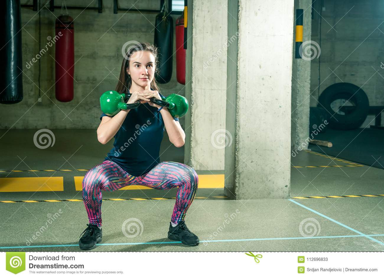 Pretty And Handsome Young Girl Holding Two Kettle Bells In