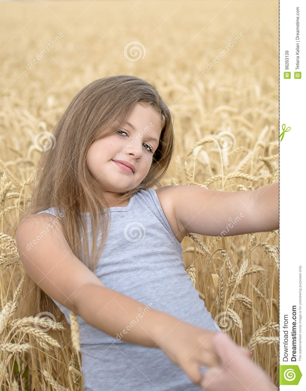 A pretty happy girl Holding the mother`s hands in golden wheat field. Concept of purity, growth, happiness