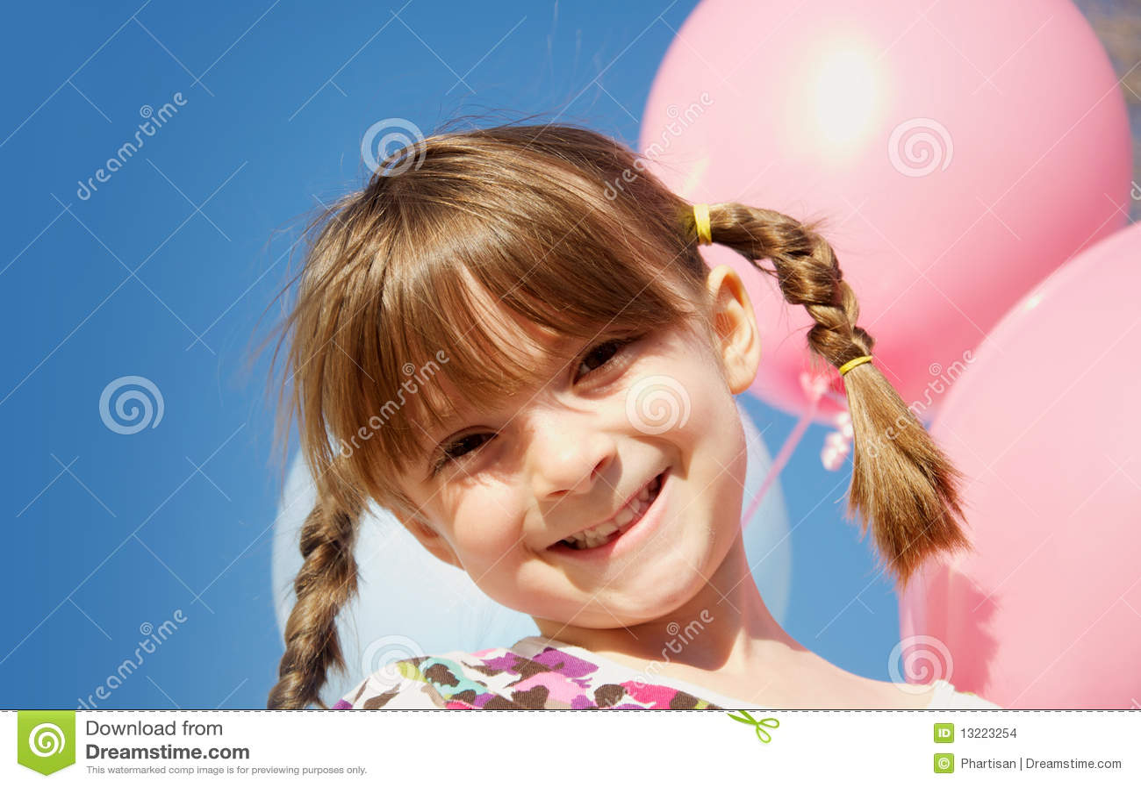 Pretty happy little girl holding balloons