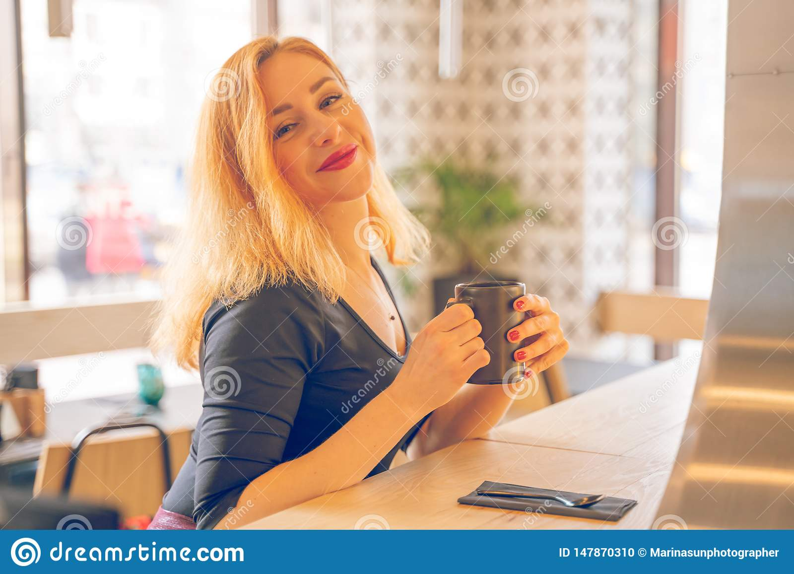 Pretty happy redheaded caucasian woman in black shirt drinks cup of coffee in the modern cafe alone