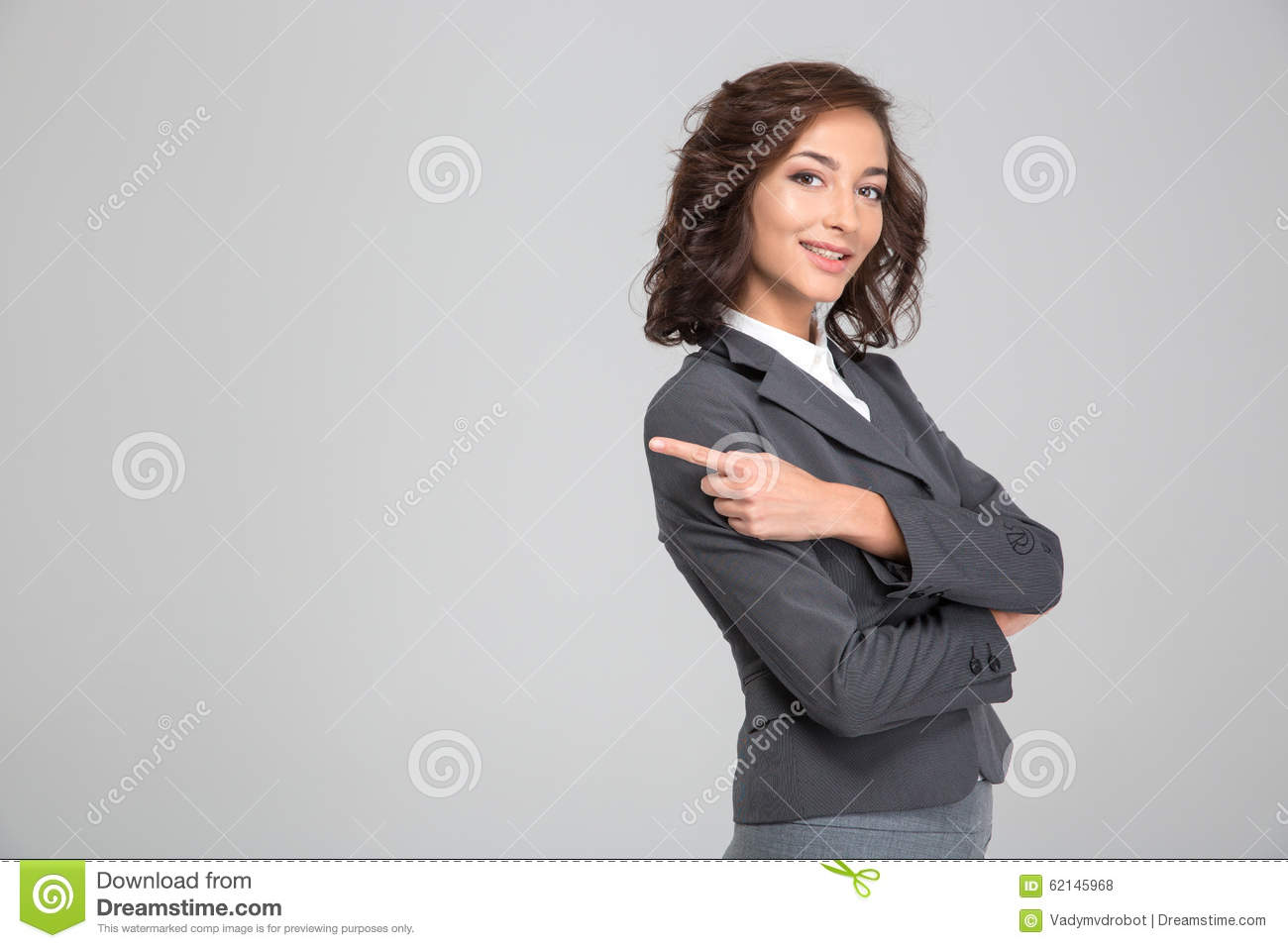 Pretty happy woman crossed arms and pointing away on copyspace