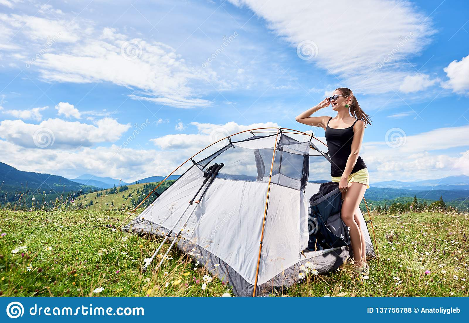 Woman tourist hiking in mountain trail, enjoying summer sunny morning in mountains near tent