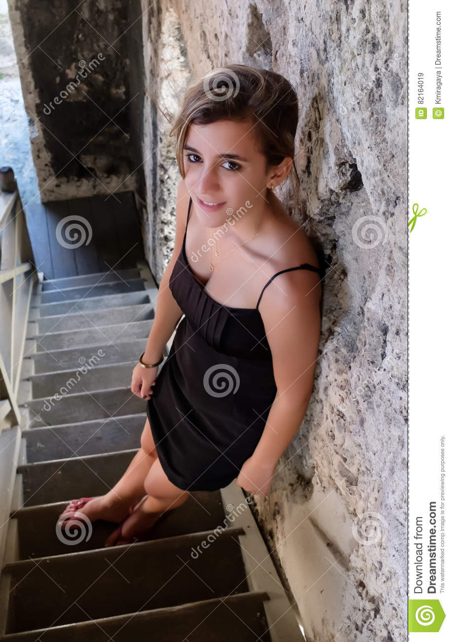 Pretty hispanic teenage girl standing on an old wooden staircase