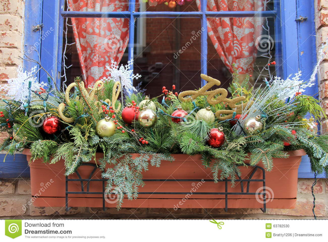 pretty holiday window box with christmas ornaments and greenery attached to colorful blue trimmed window of brick home
