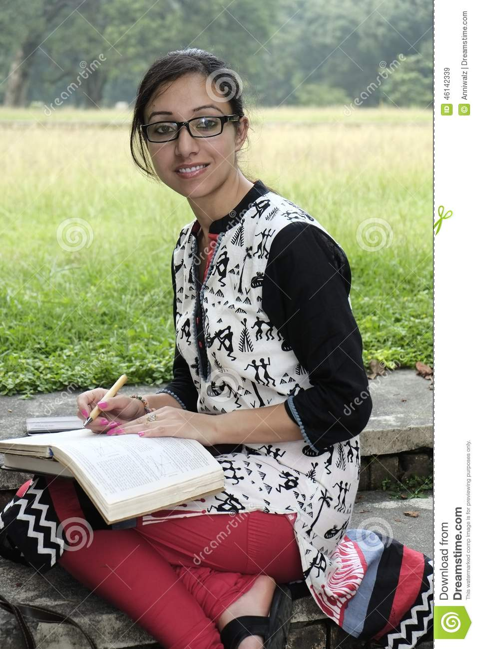 pretty indian college student studying in college campus wearing