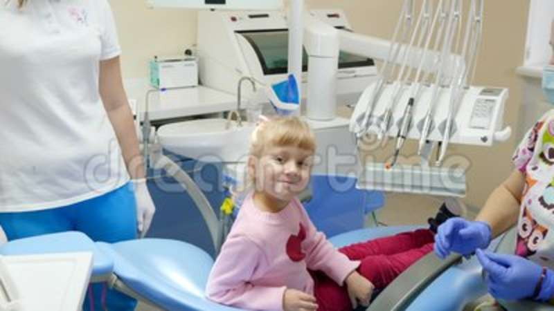 Brilliant Pretty Kid After Treatment Teeth Waving Arm While Sitting On Dental Chair Next To Stomatologist In Rubber Gloves And Andrewgaddart Wooden Chair Designs For Living Room Andrewgaddartcom