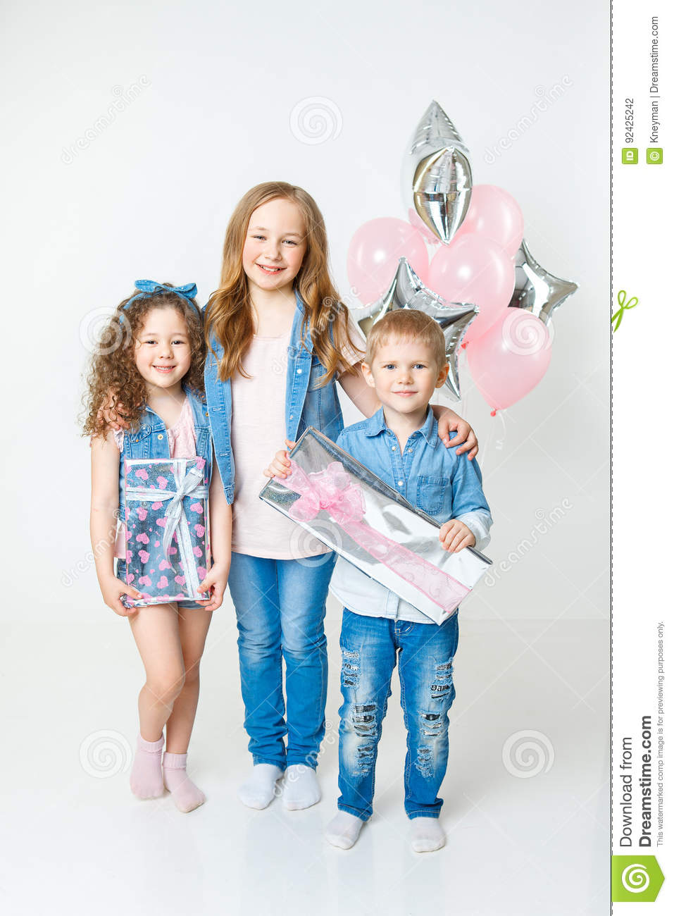 Pretty kids on birthday party stay with presents in jeans clothes. Balloons. Smiling
