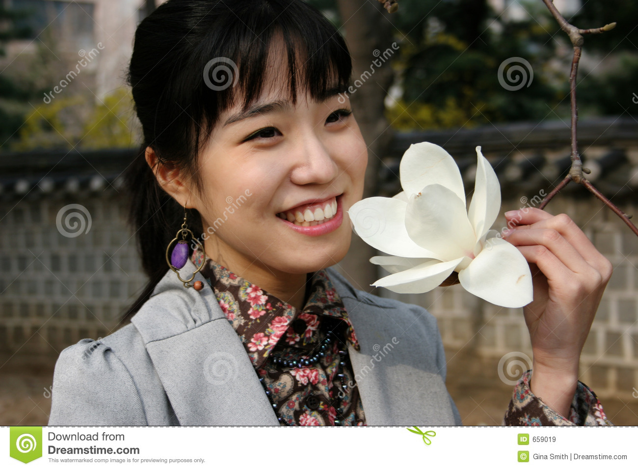 Pretty Korean woman holding a flower in spring