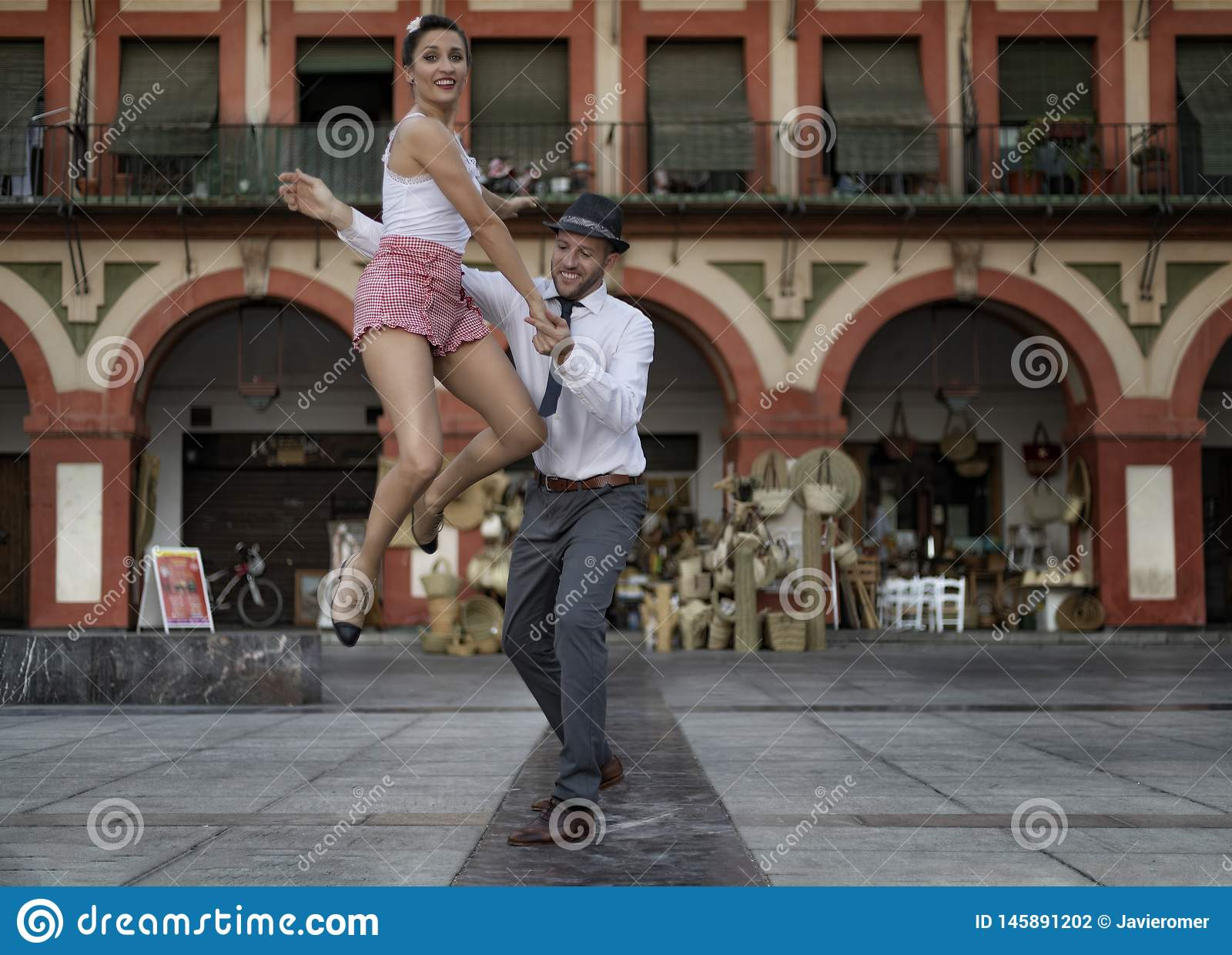 Pretty lindy hop dancer jumped while dancing with her partner