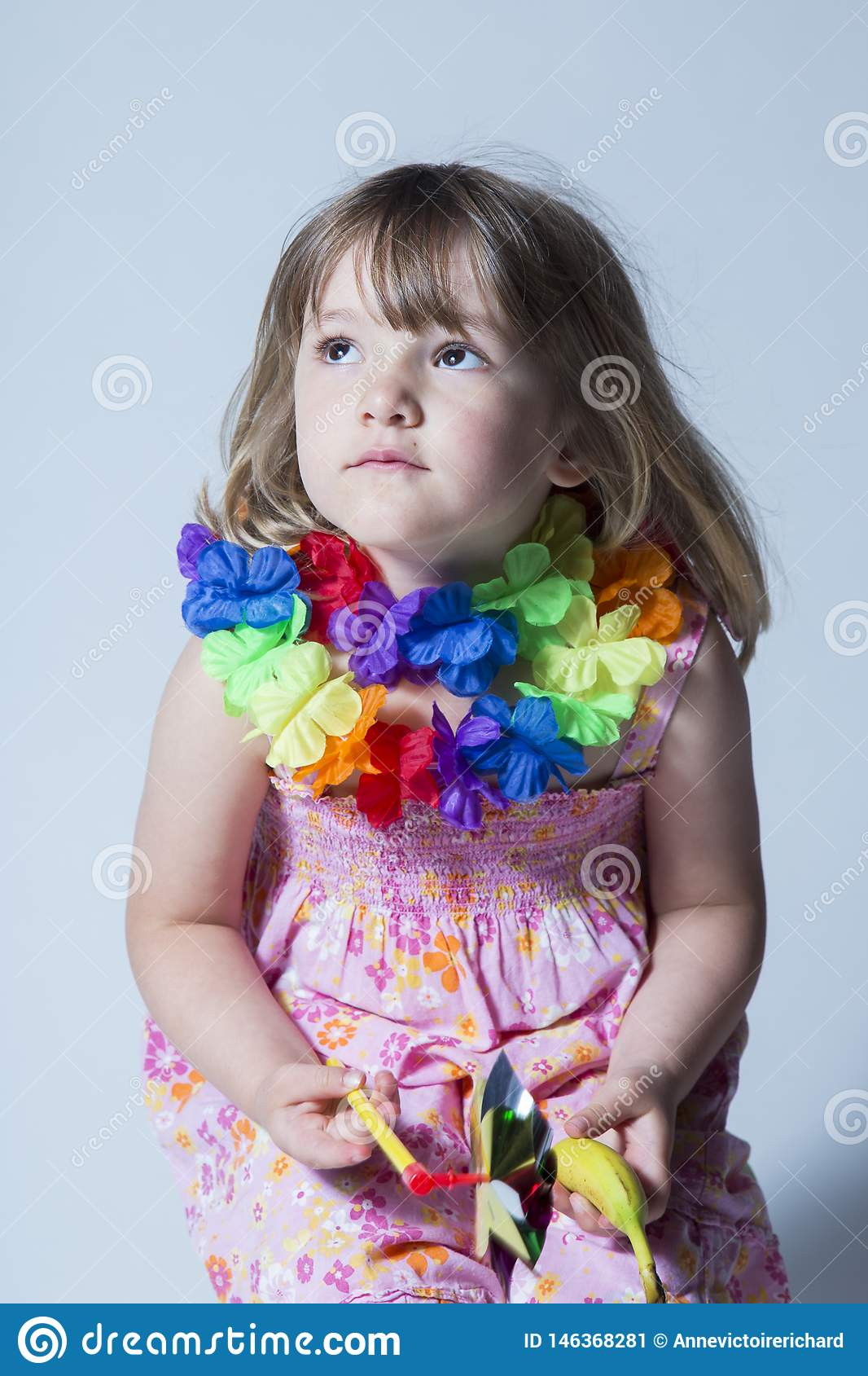 Pretty little girl dressed in pink floral dress and silk flower garland sitting on stool