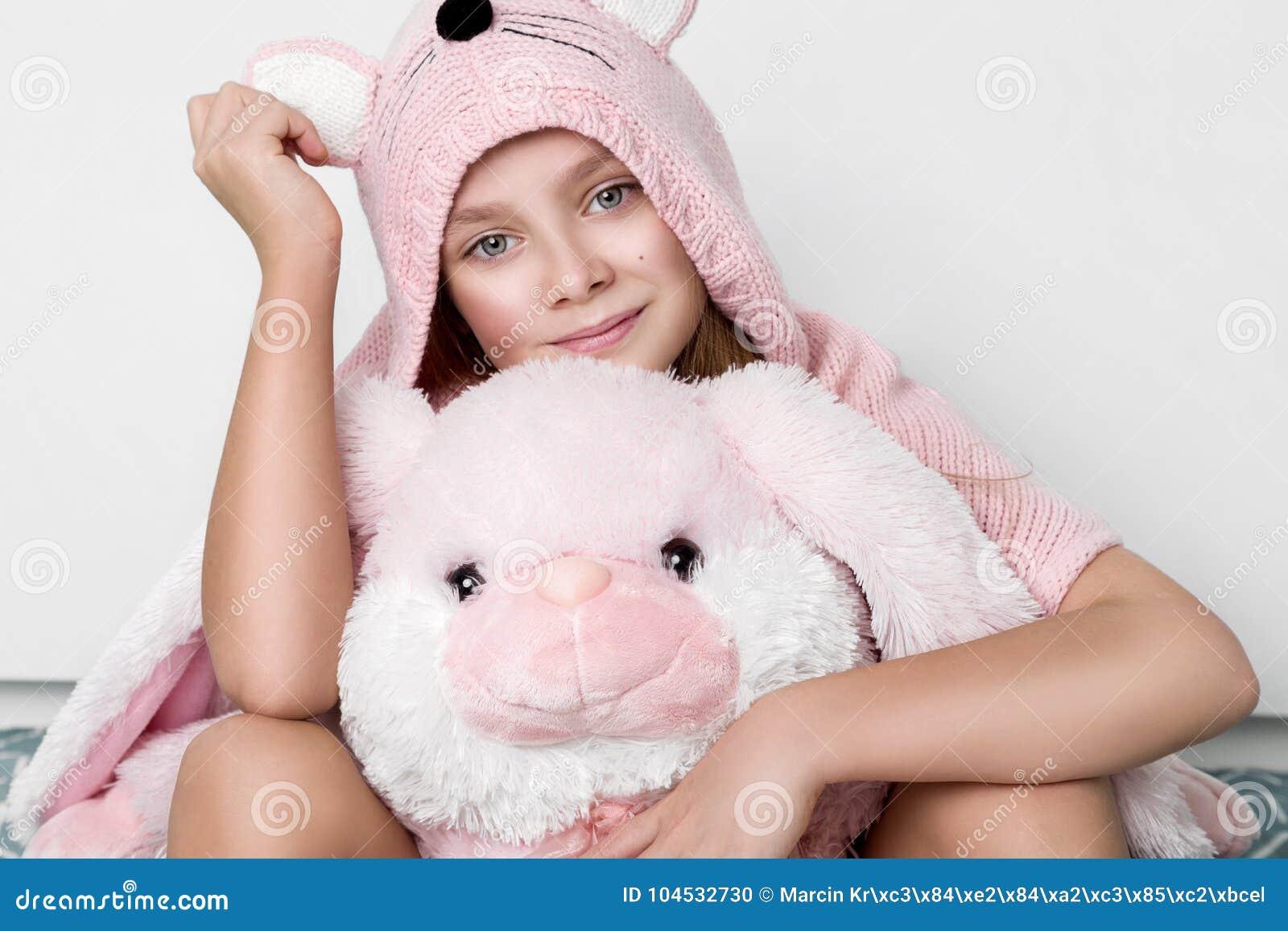 Pretty Little Girl Wearing A Warm Sweater With Rabbit Ears Sitting