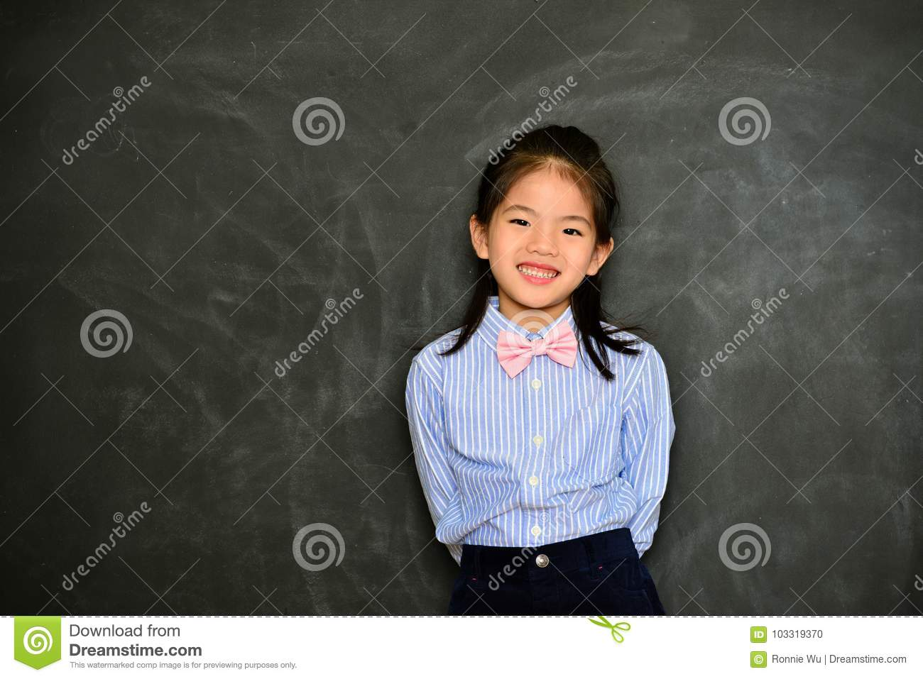 c5eec4ee141b Beautiful pretty little girl kid dress up as school teacher standing in  chalk blackboard background.