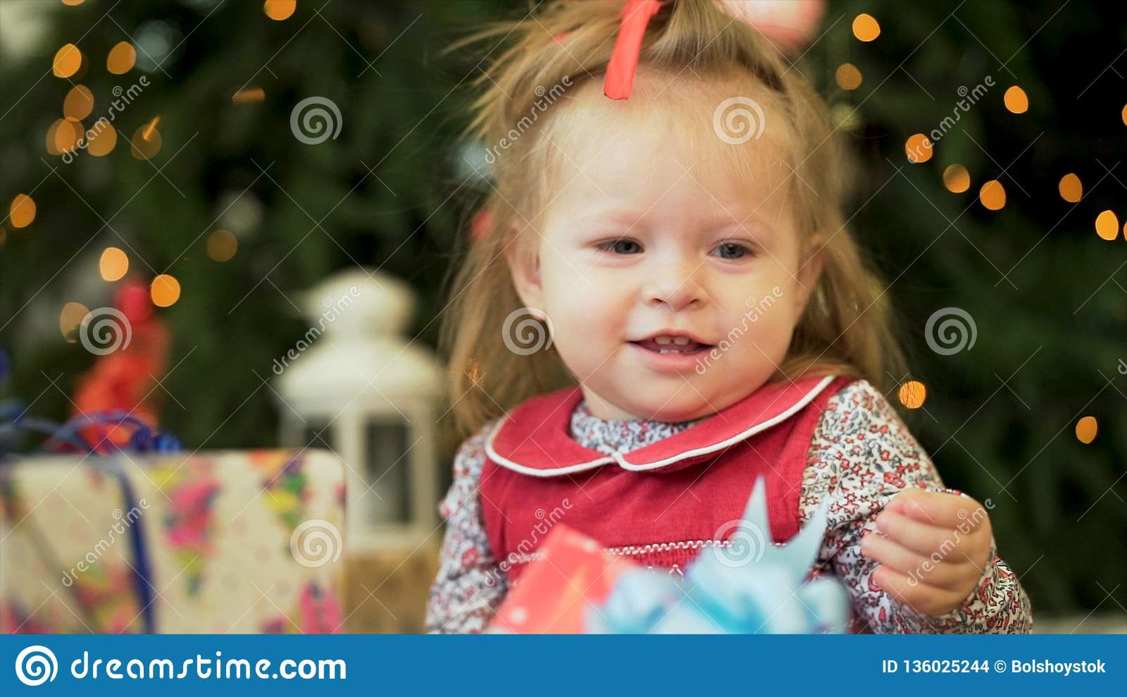 Pretty little girl near the new year tree. Little girl smiles and play with gifts on the background of Christmas trees
