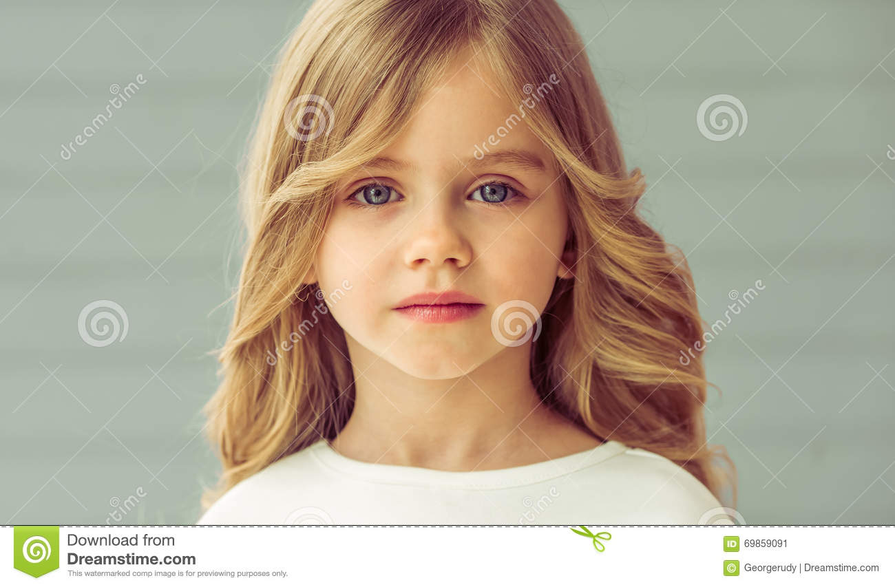 a51e6d6ec00 Portrait of pretty little blonde girl with beautiful big eyes looking at  camera