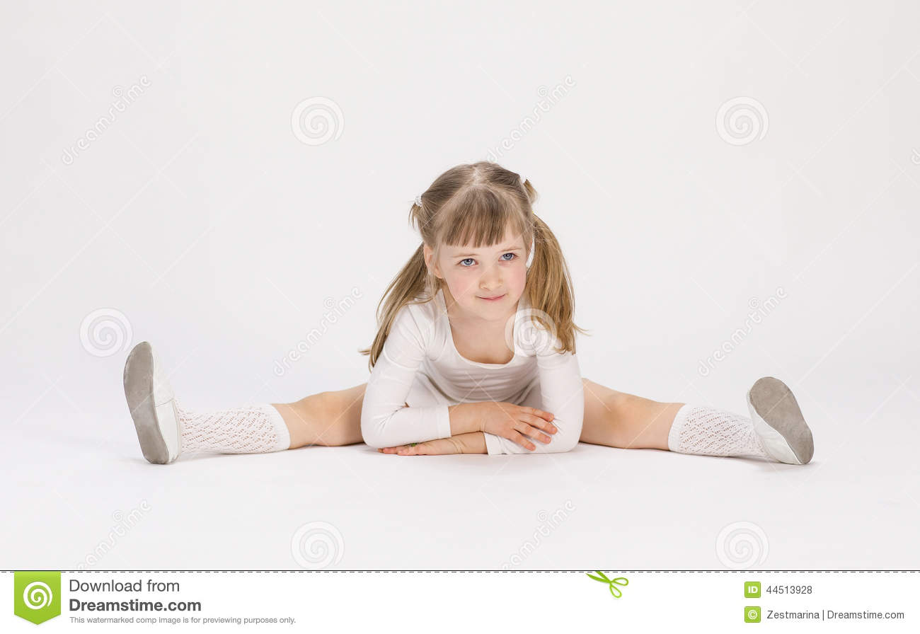 Pretty Little Girl Sitting On The Floor And Doing Exercise