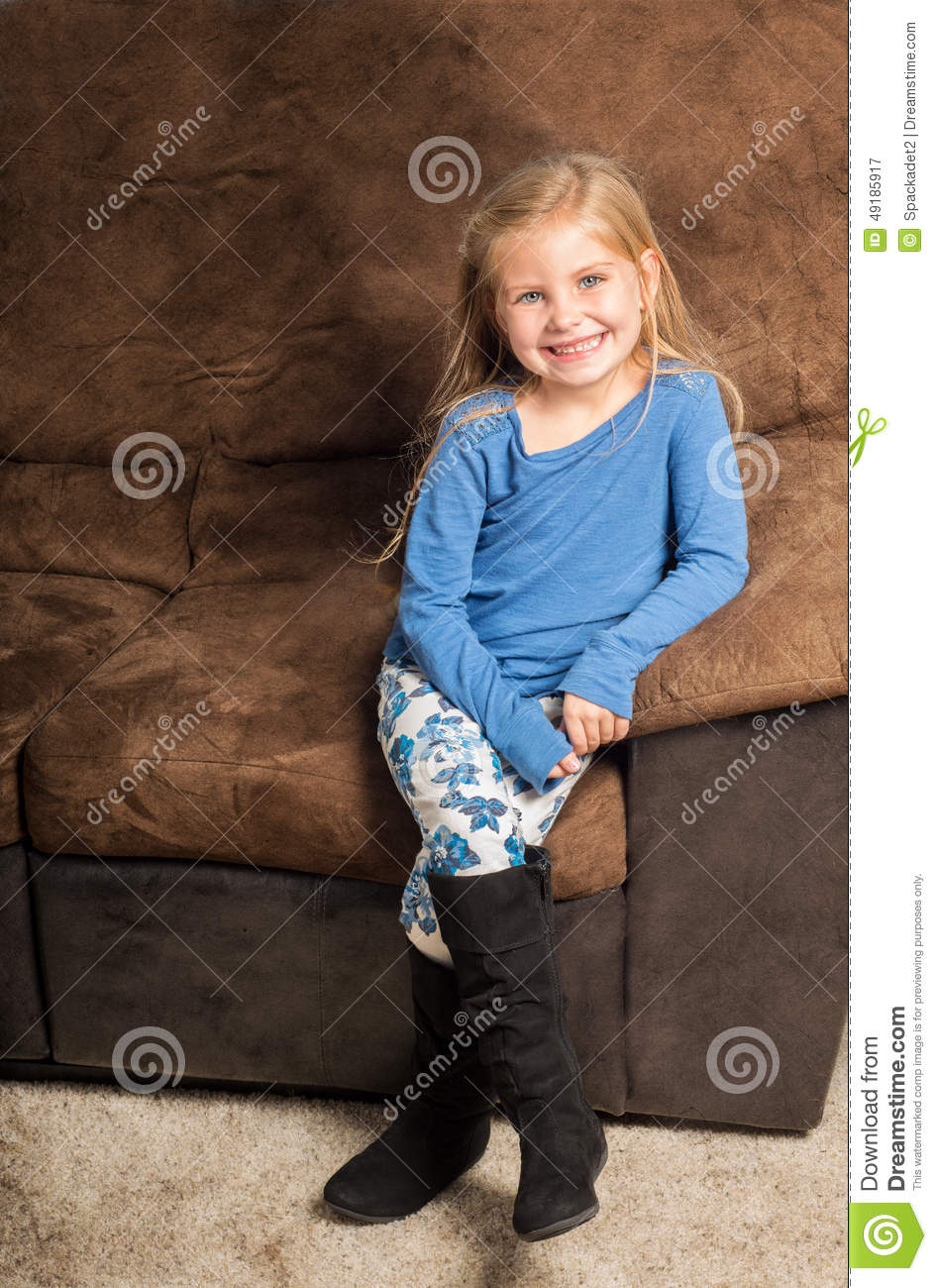 Pretty Little Girl Sitting On A Sofa With A Big Smile ...
