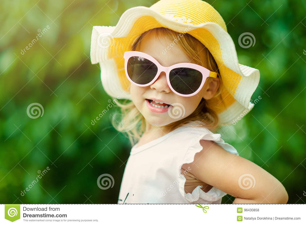 Pretty little girl in a striped dress and hat relaxing on the beach near sea, summer, vacation, travel concept. smiling