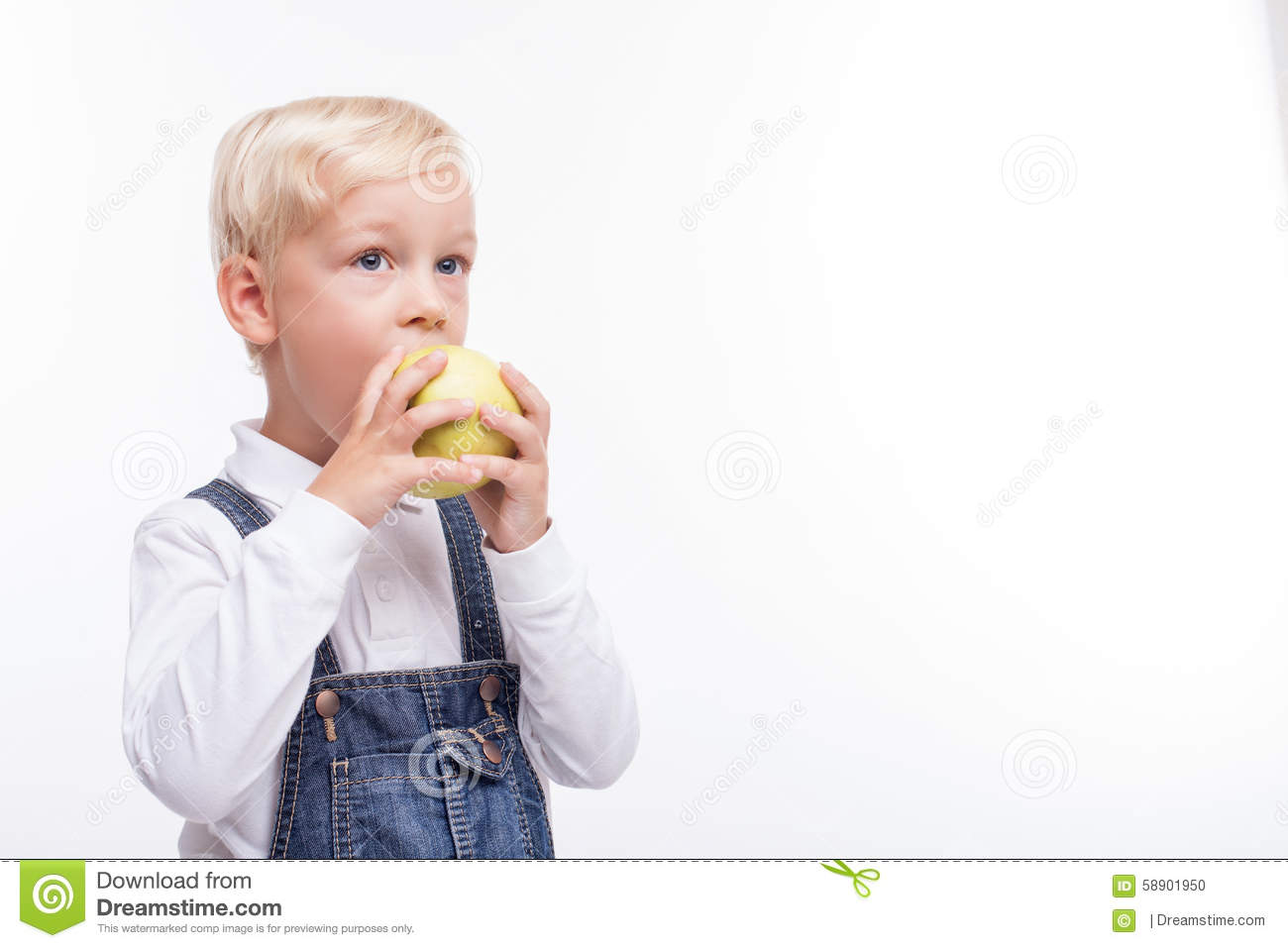 Pretty male child is eating green fruit