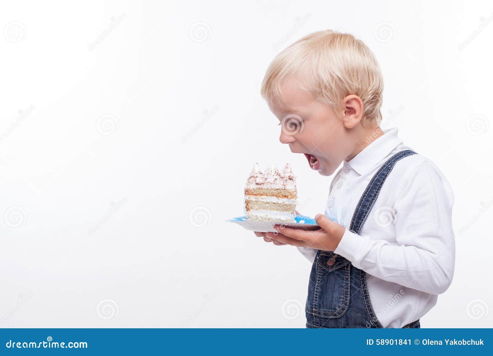 Pretty male child is tasting sweet food