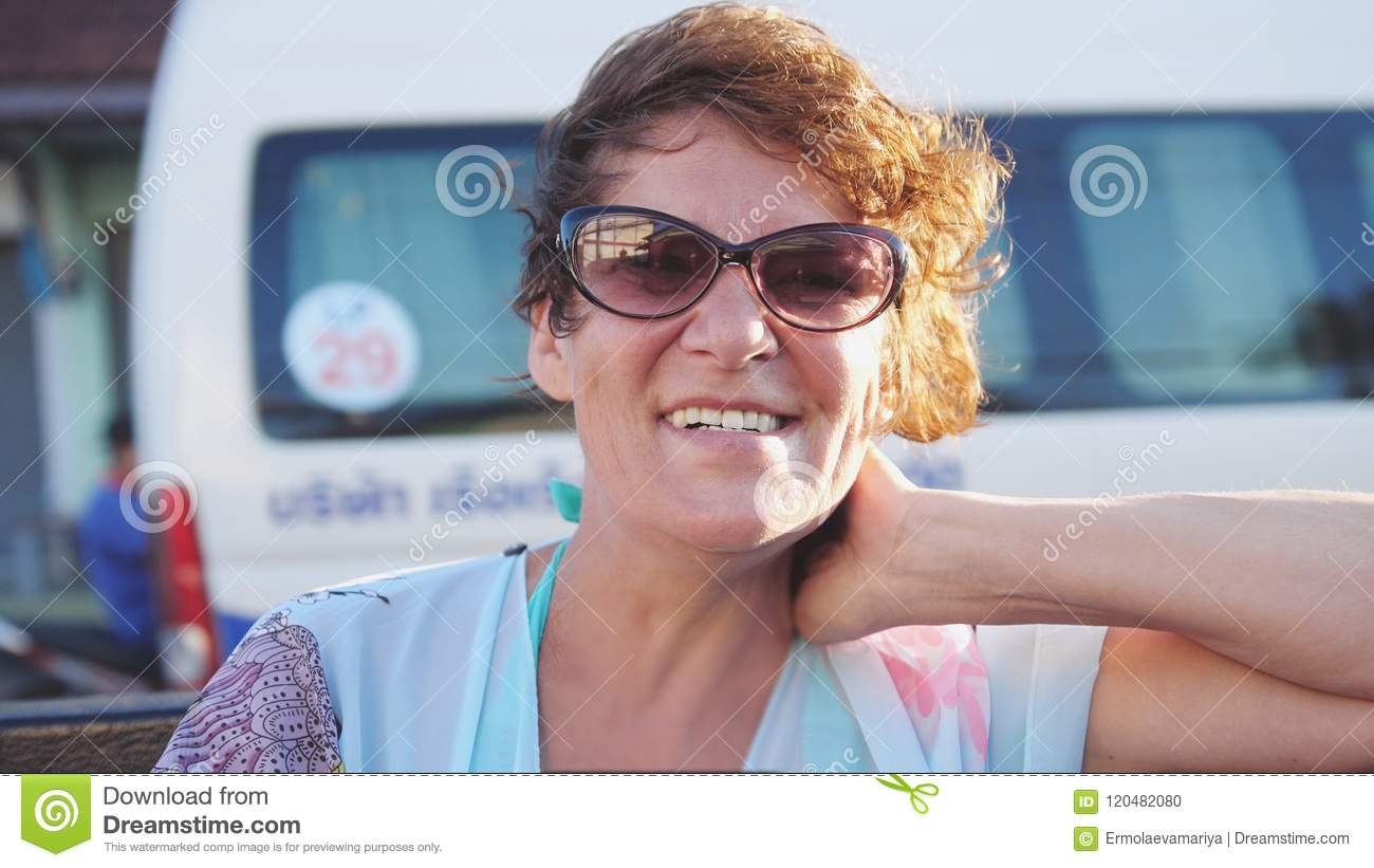 Pretty mature woman in aged wearing sunglasses enjoying summer sun. Happy  smiling woman having fun