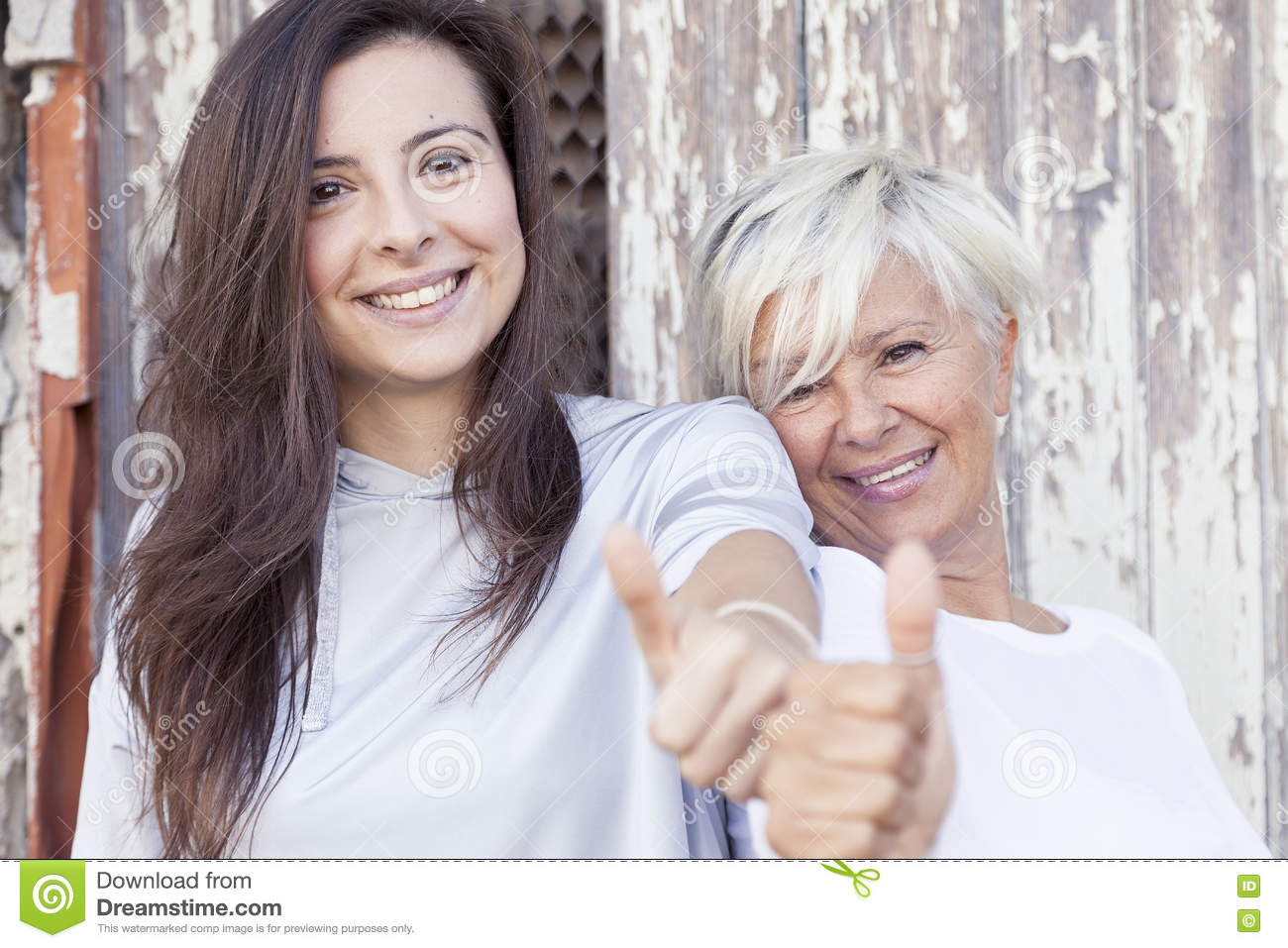 Pretty mother and adult daughter make the sign
