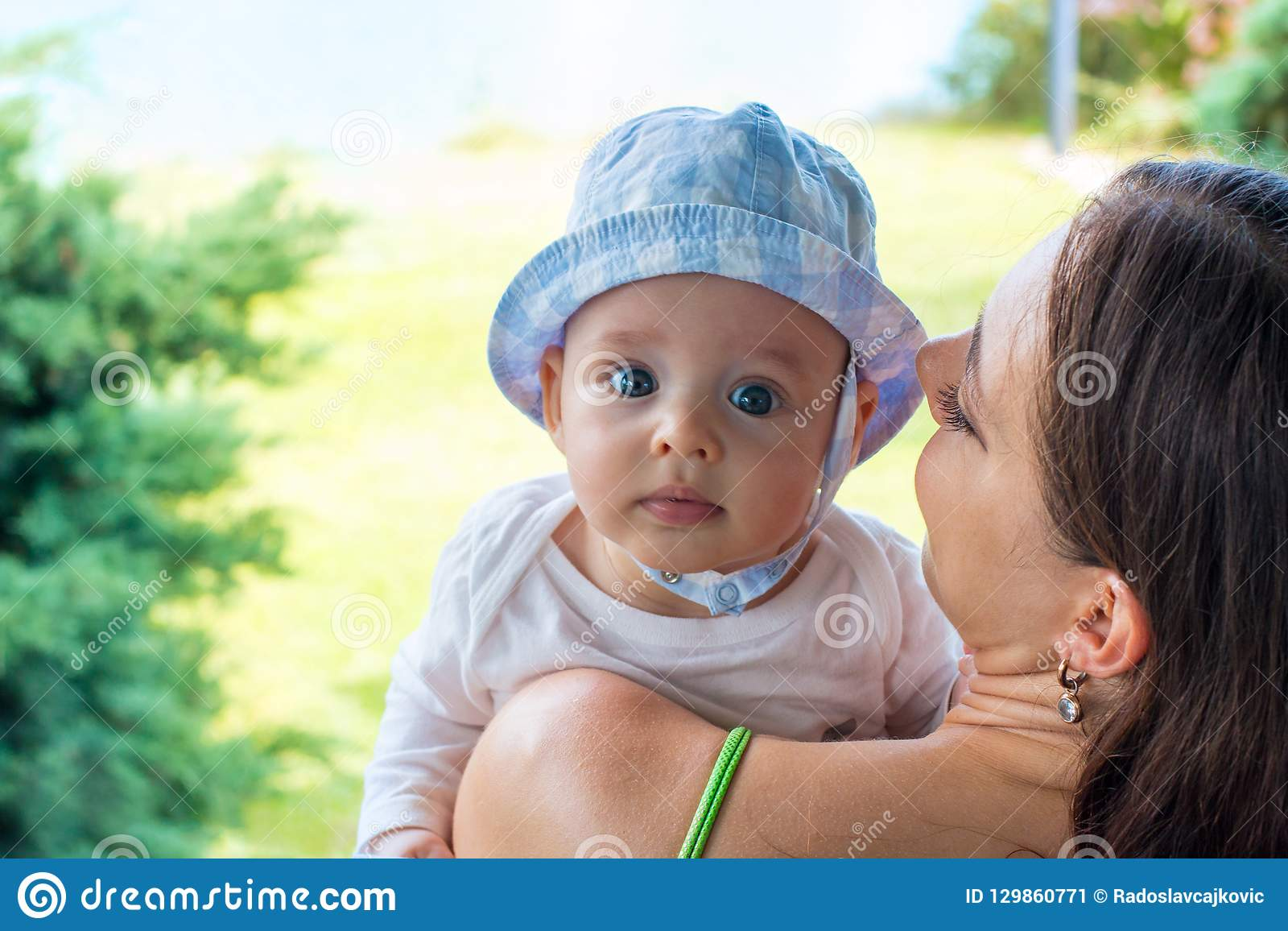 Pretty mother cuddle cute blue eyed baby in hat, infant face portrait