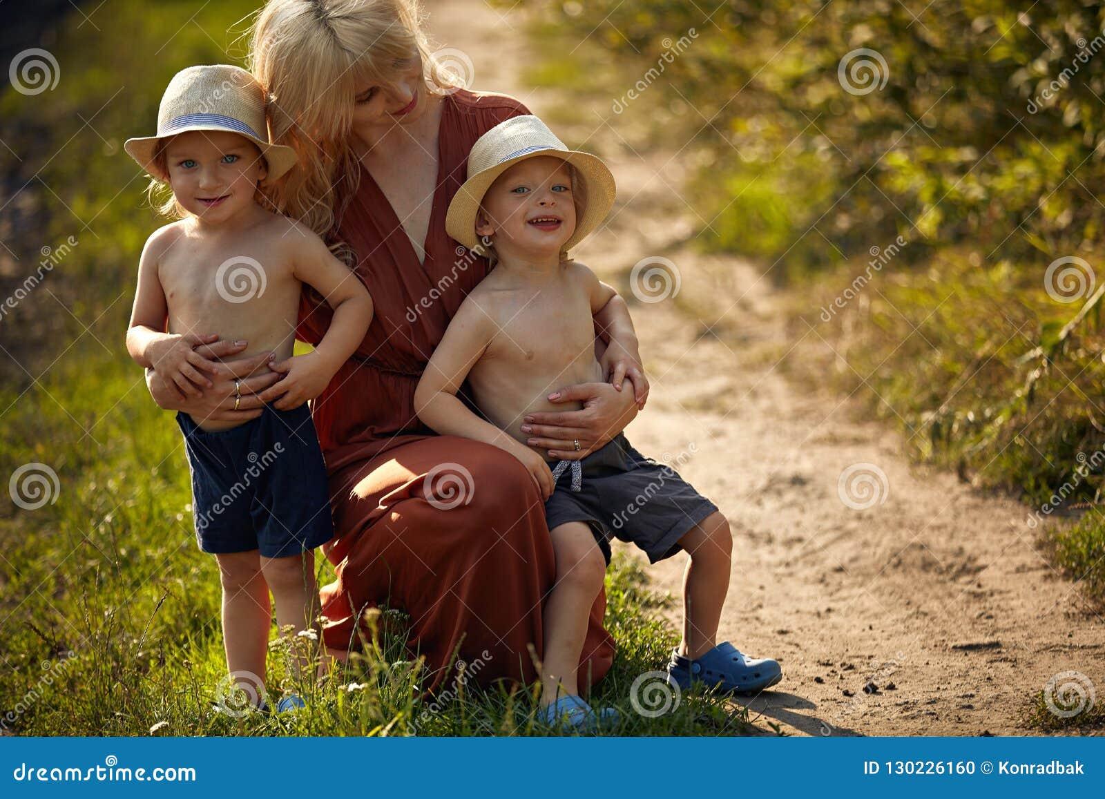 Pretty mother hugging her beloved sons