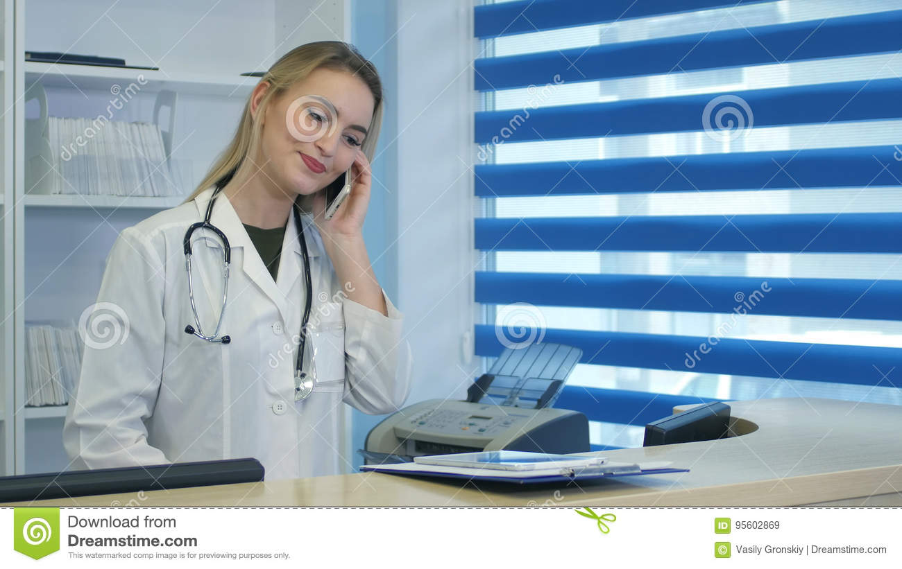 Pretty nurse using tablet and phone at hospital reception desk