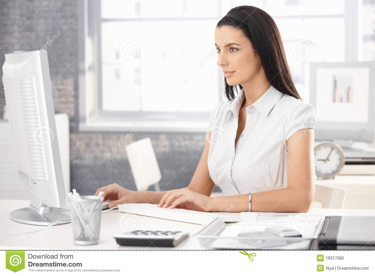 Pretty office worker girl sitting at desk in office, using desktop ...