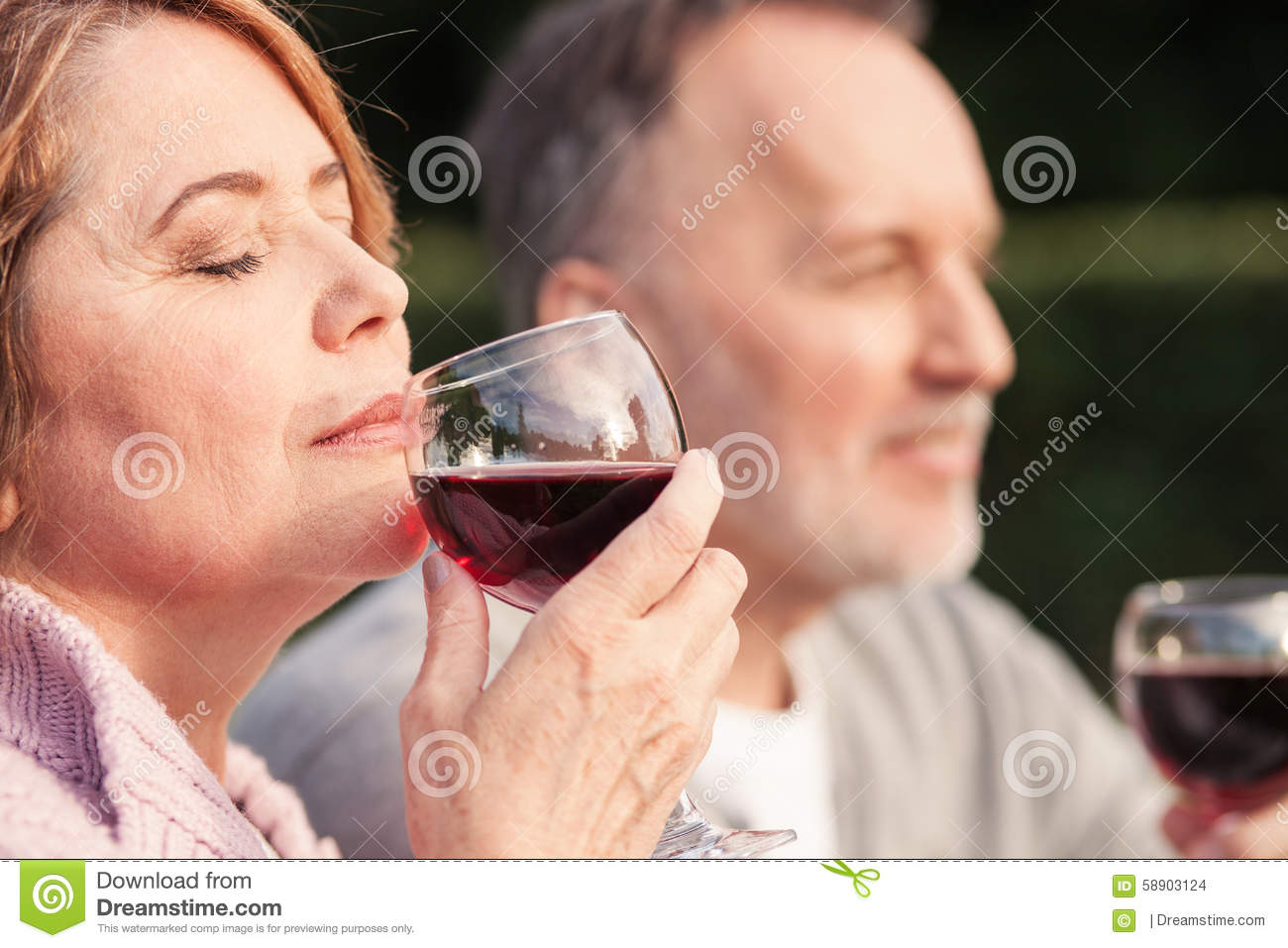 Pretty old loving couple is relaxing in the nature