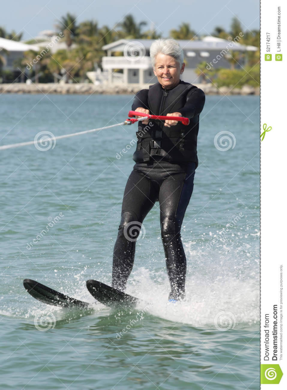 Pretty Older Lady Water Skiing by Nice House.