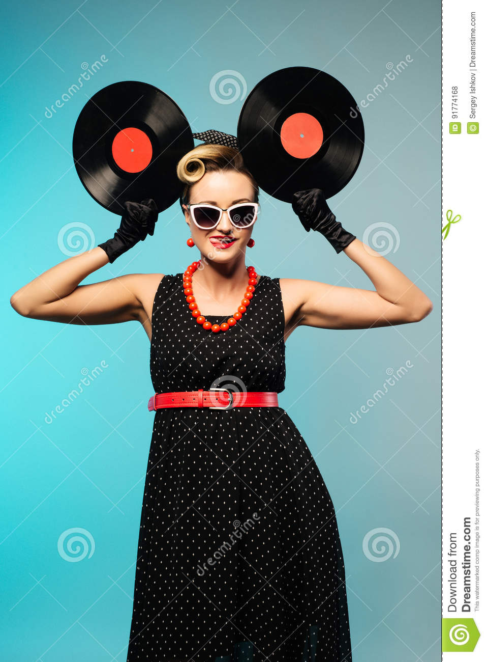 Pretty pin-up woman with retro hairstyle and make-up posing with vinyl record over blue background.