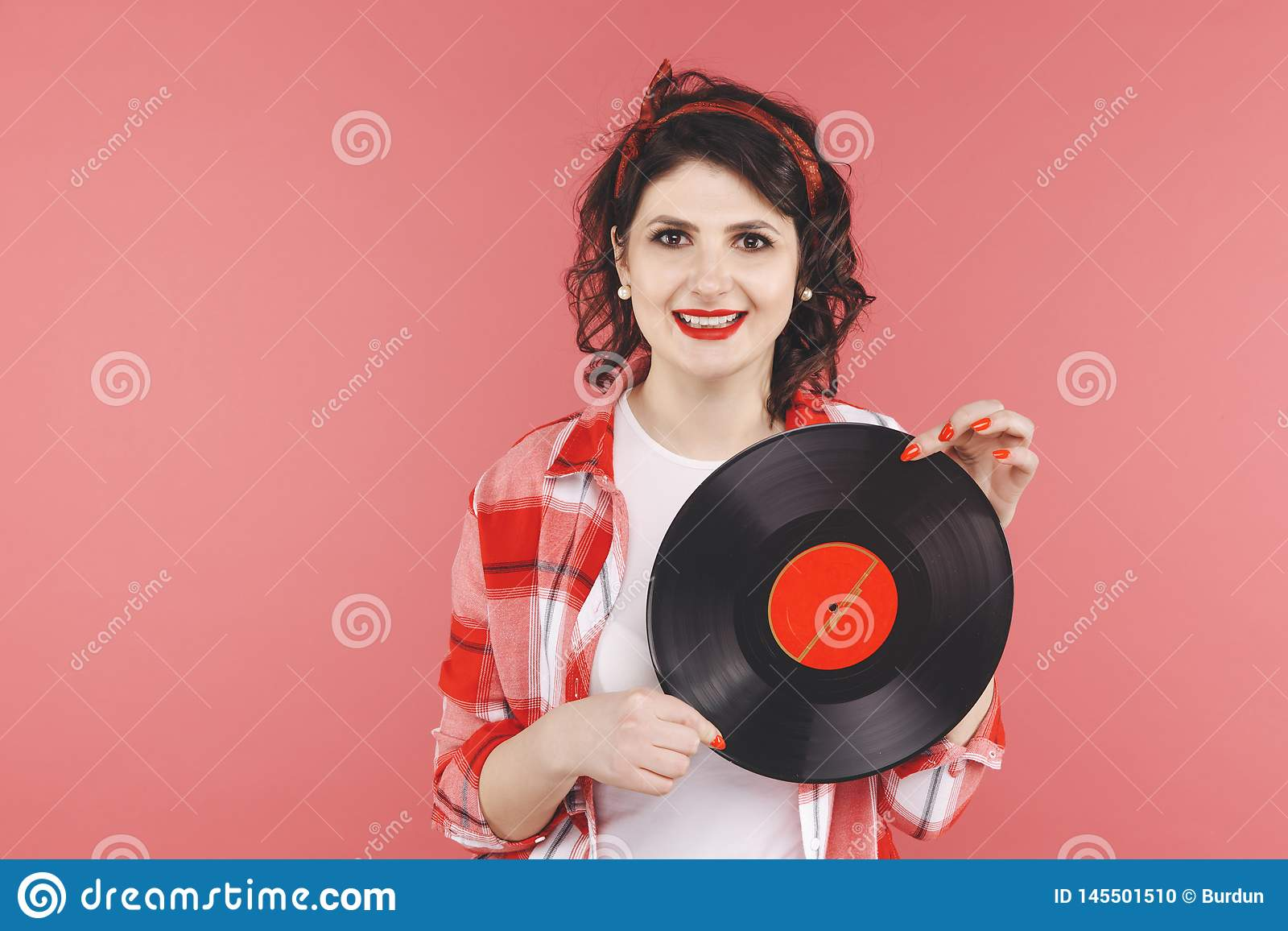 Pretty pin up woman with vinyl isolated over thered backgruond.