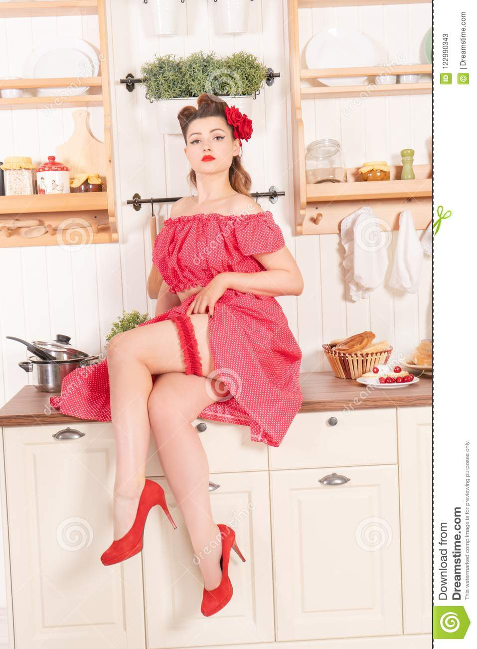 00630c755 Beautiful young girl with flower in her hair posing in red pin up polka dot  dress